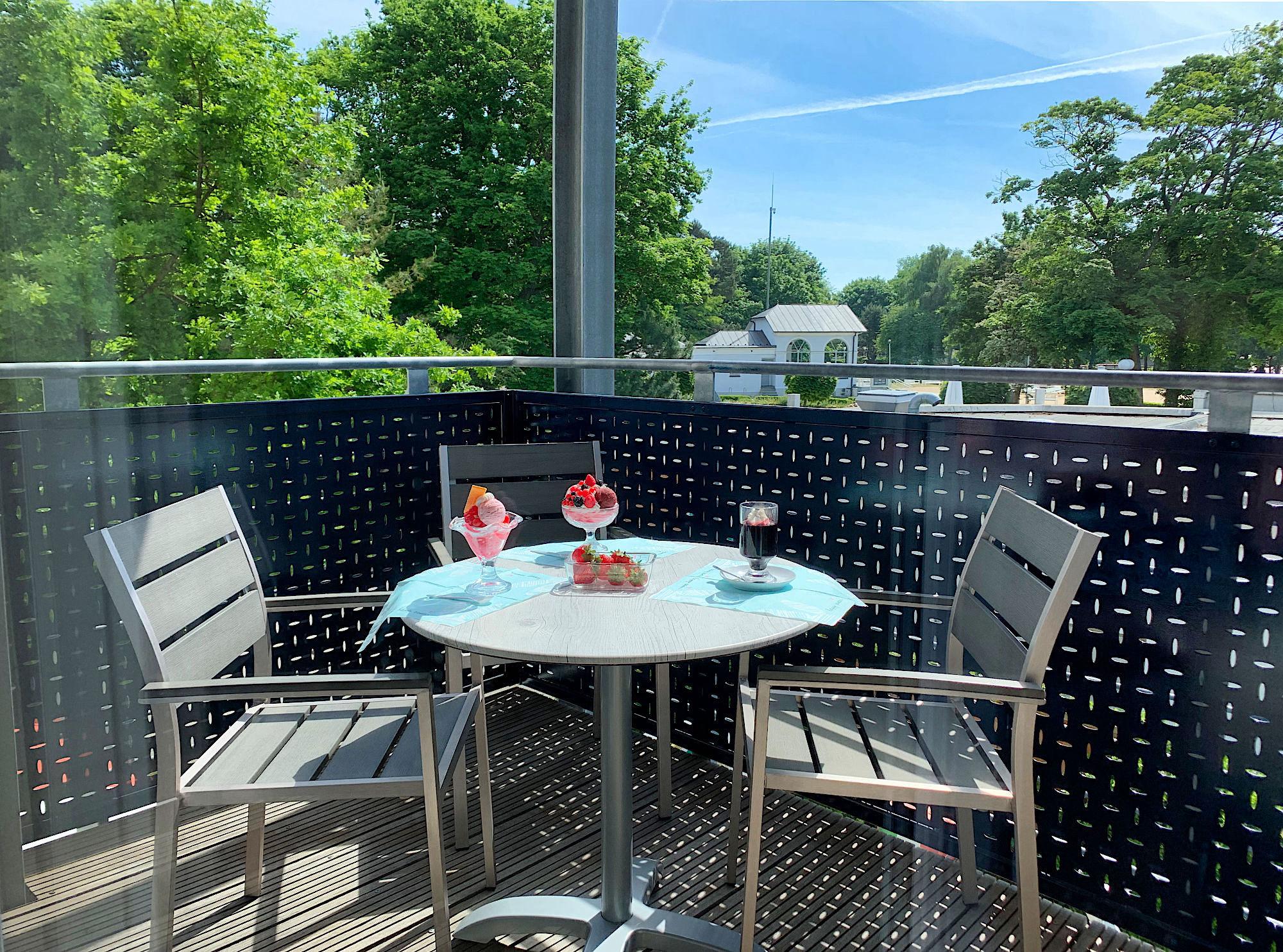 Balkon mit Tisch und Stühlen, im Hintergrund ist der Kurpark mit der Kurmuschel zu sehen