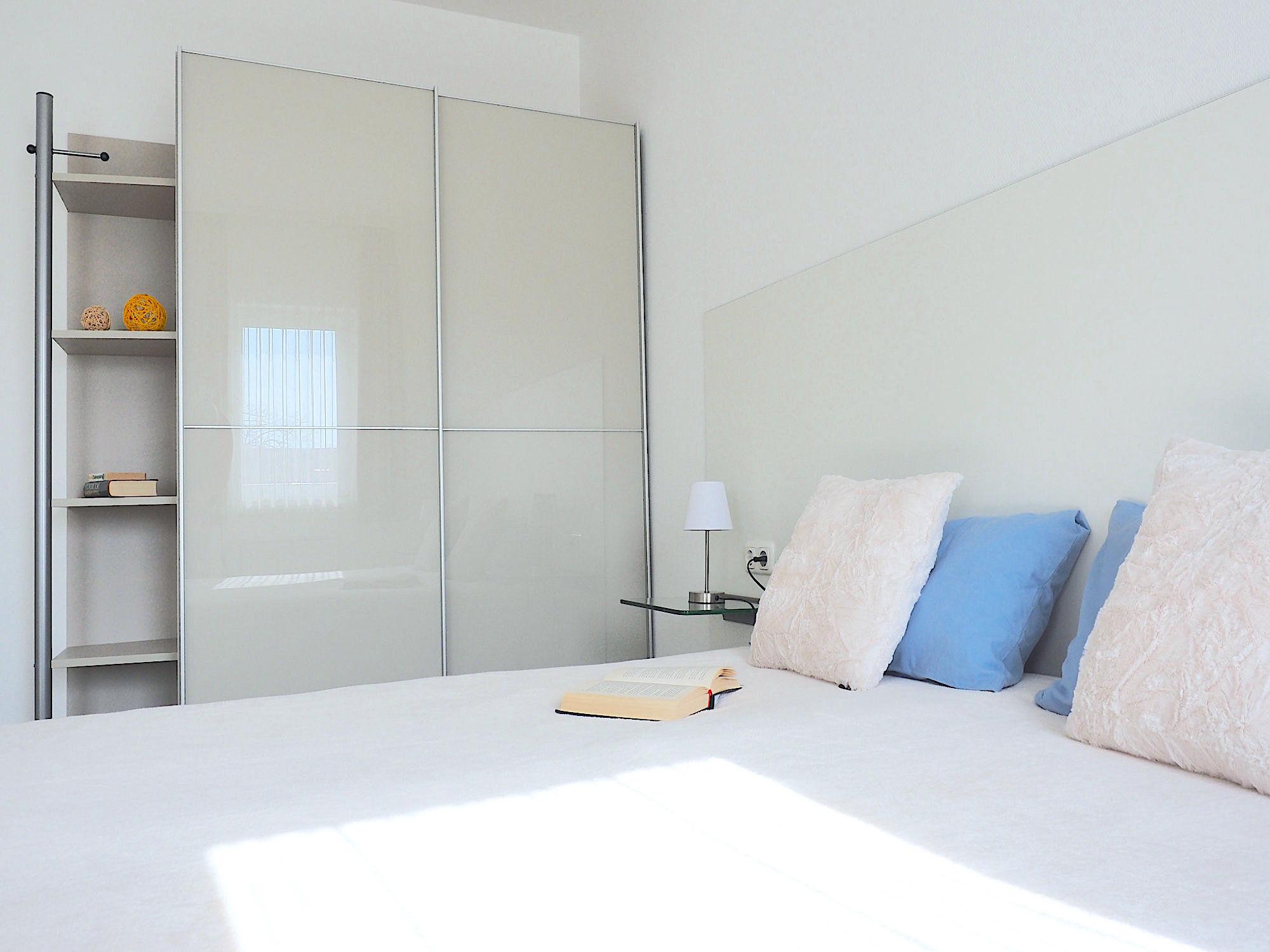 Schlafzimmer mit Doppelbett, links davon ein großer Kleiderschrank
