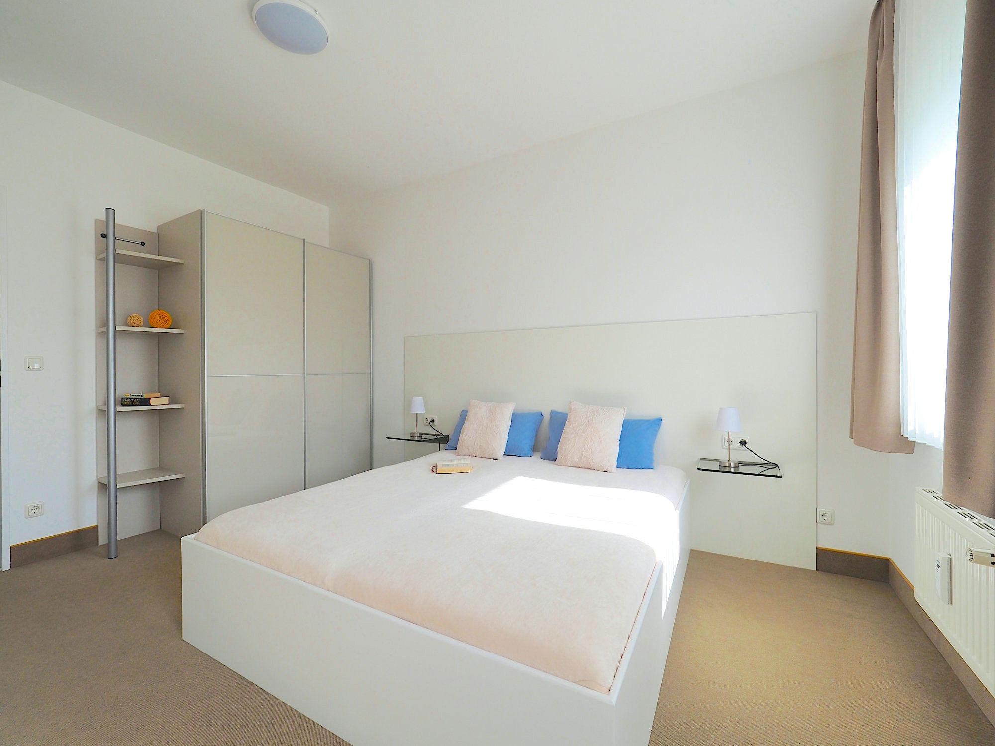 Schlafzimmer mit Doppelbett, links davon ein großer Kleiderschrank, rechts ein Fenster