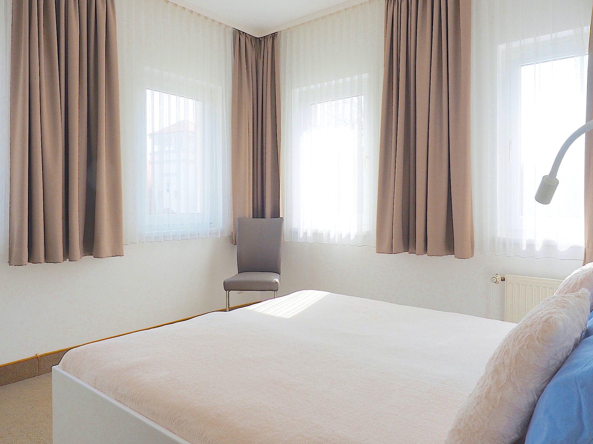Schlafzimmer mit Doppelbett und Blick zu drei Fenstern