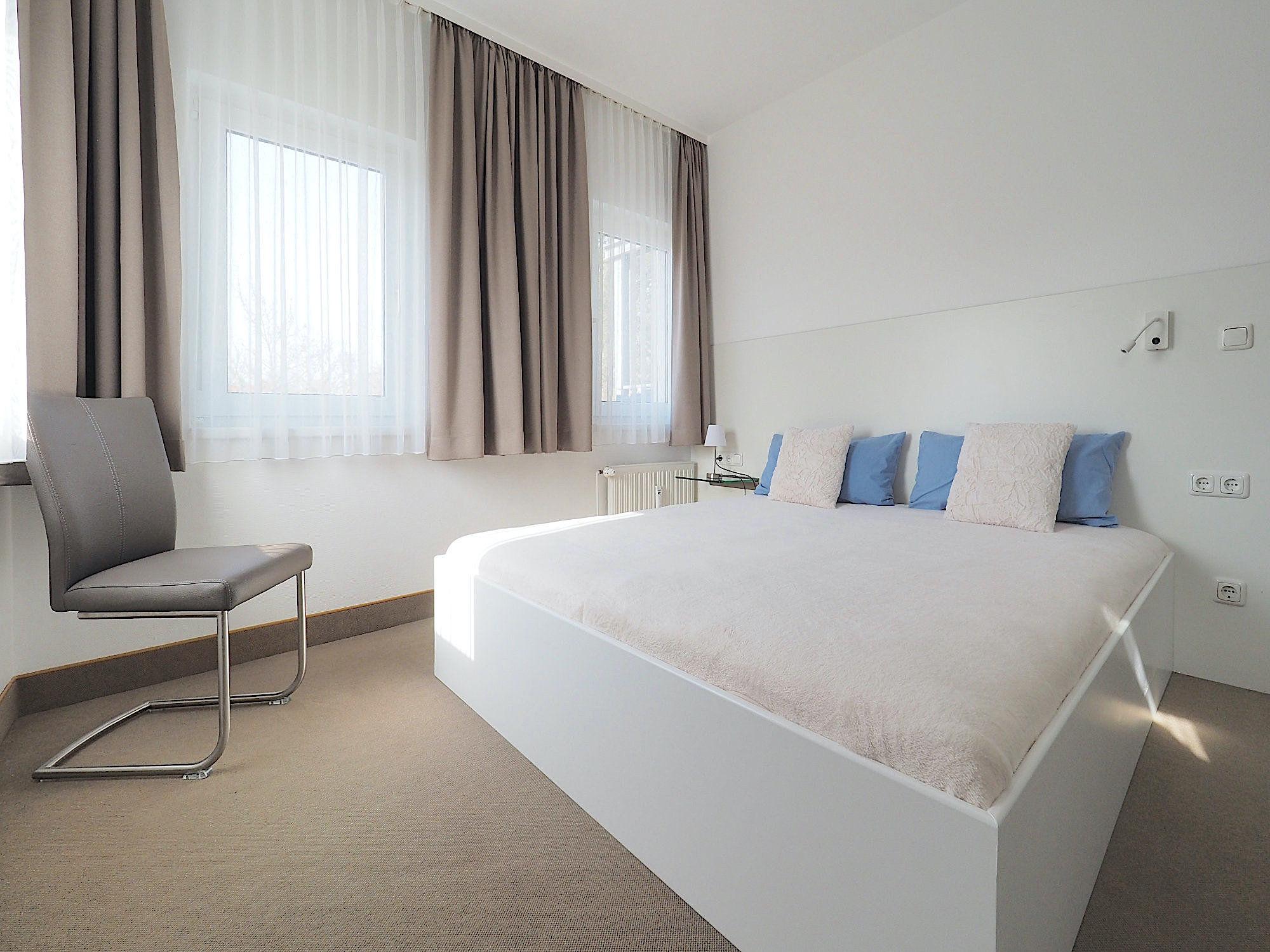 Schlafzimmer mit Doppelbett, im Hintergrund 2 Fenster