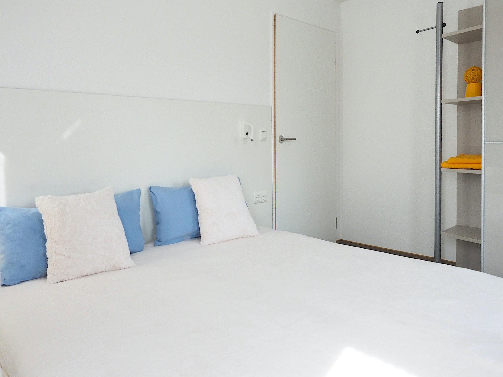 Schlafzimmer mit Doppelbett, Kopfteil. Rechts davon Regal als Bestandteil von einem Kleiderschrank