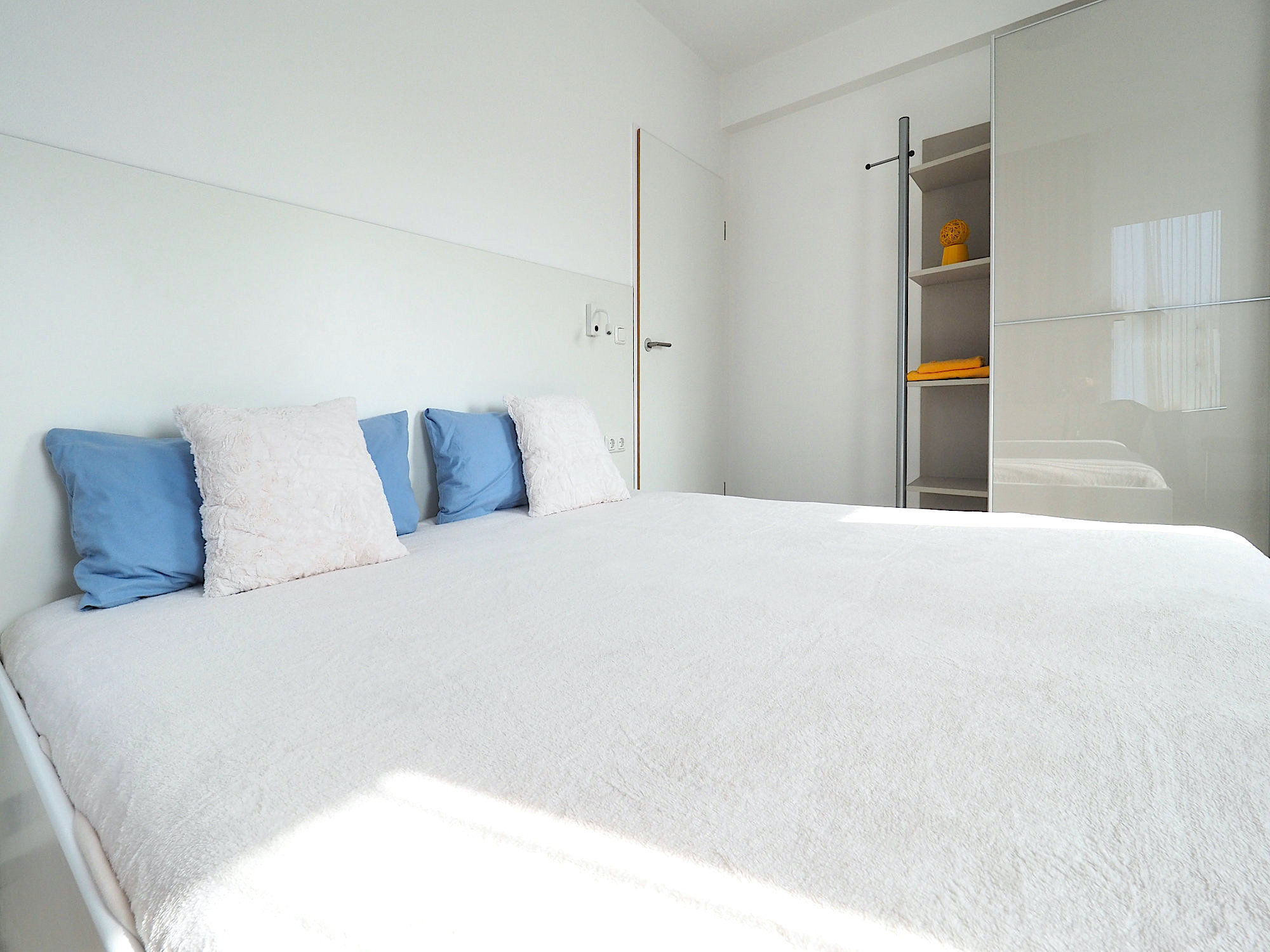 Schlafzimmer mit Doppelbett, rechts davon großer Kleiderschrank mit Regalteil