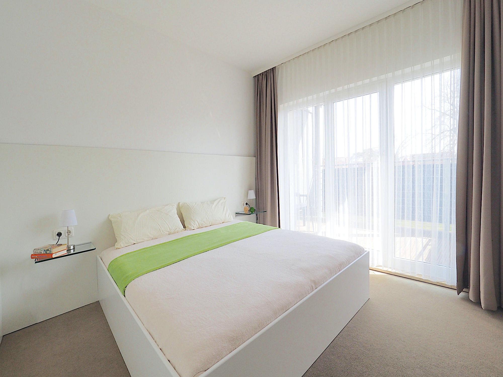 Zweites Schlafzimmer mit Doppelbett, im Hintergrund bodentiefe Fenster