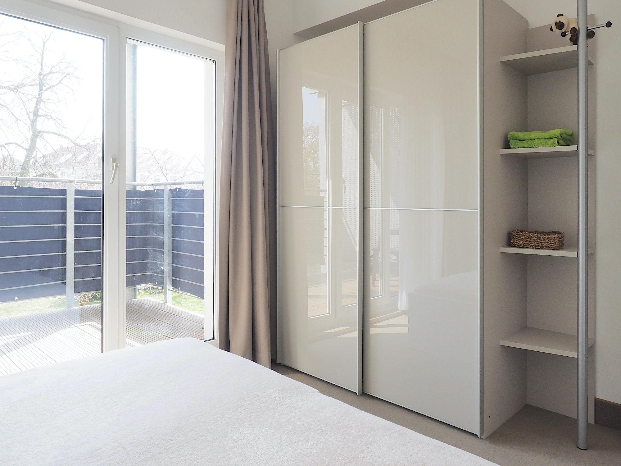 Schlafzimmer mit Doppelbett, rechts davon ein großer Kleiderschrank mit Regalteil, im Hintergrund bodentiefe Fenster