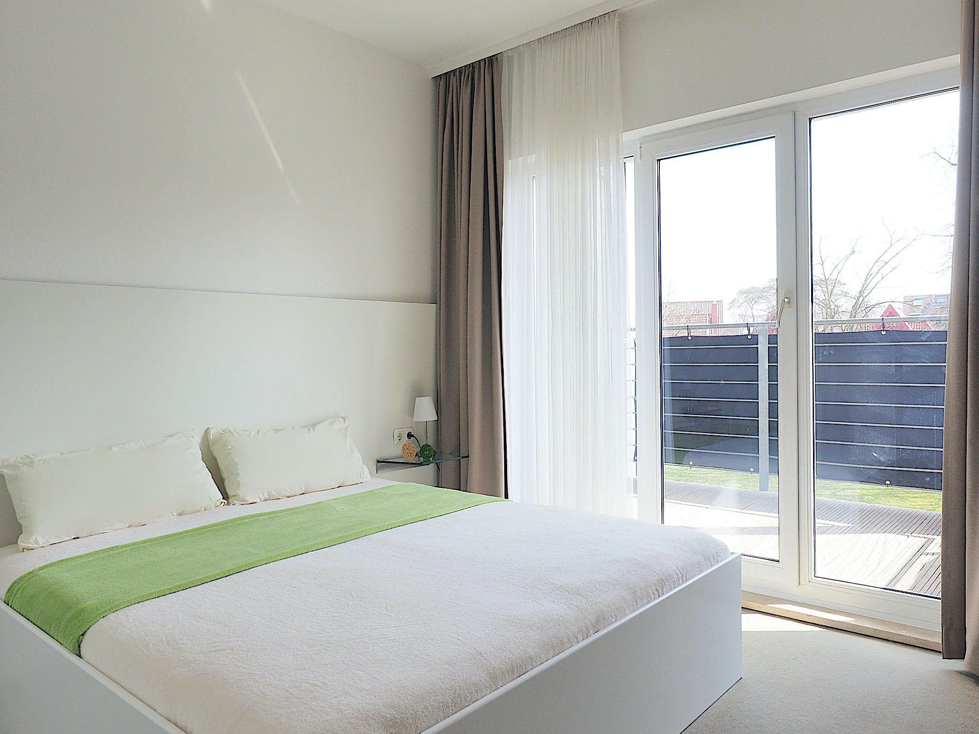 Zweites Schlafzimmer mit Doppelbett, rechts davon bodentiefe Fenster