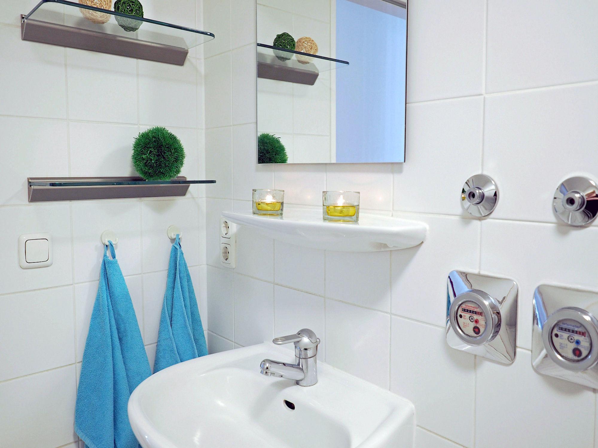 Duschbad mit Waschbecken und Spiegel sowie Glaskonsolen