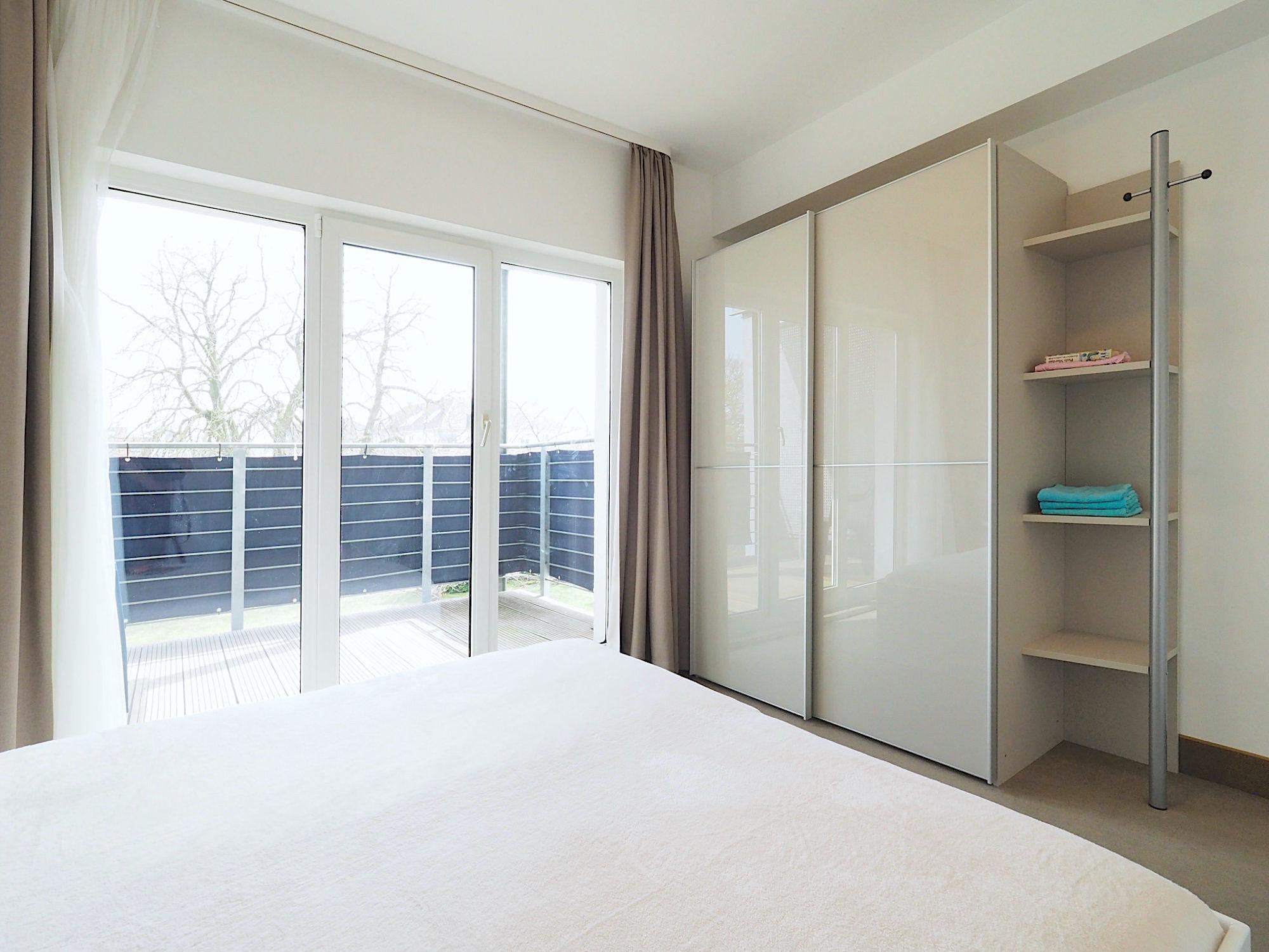 Zweites Schlafzimmer mit Doppelbett, rechts davon ein großer Kleiderschrank mit Regalteil, im Hintergrund bodentiefe Fenster