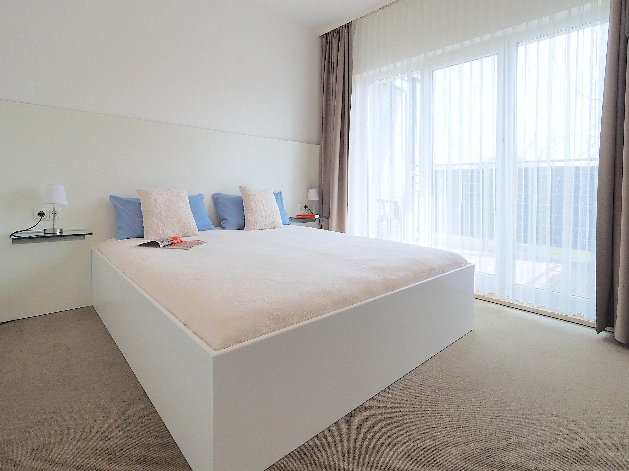 Zweites Schlafzimmer mit Doppelbett, rechts davon bodentiefe Fensterfront