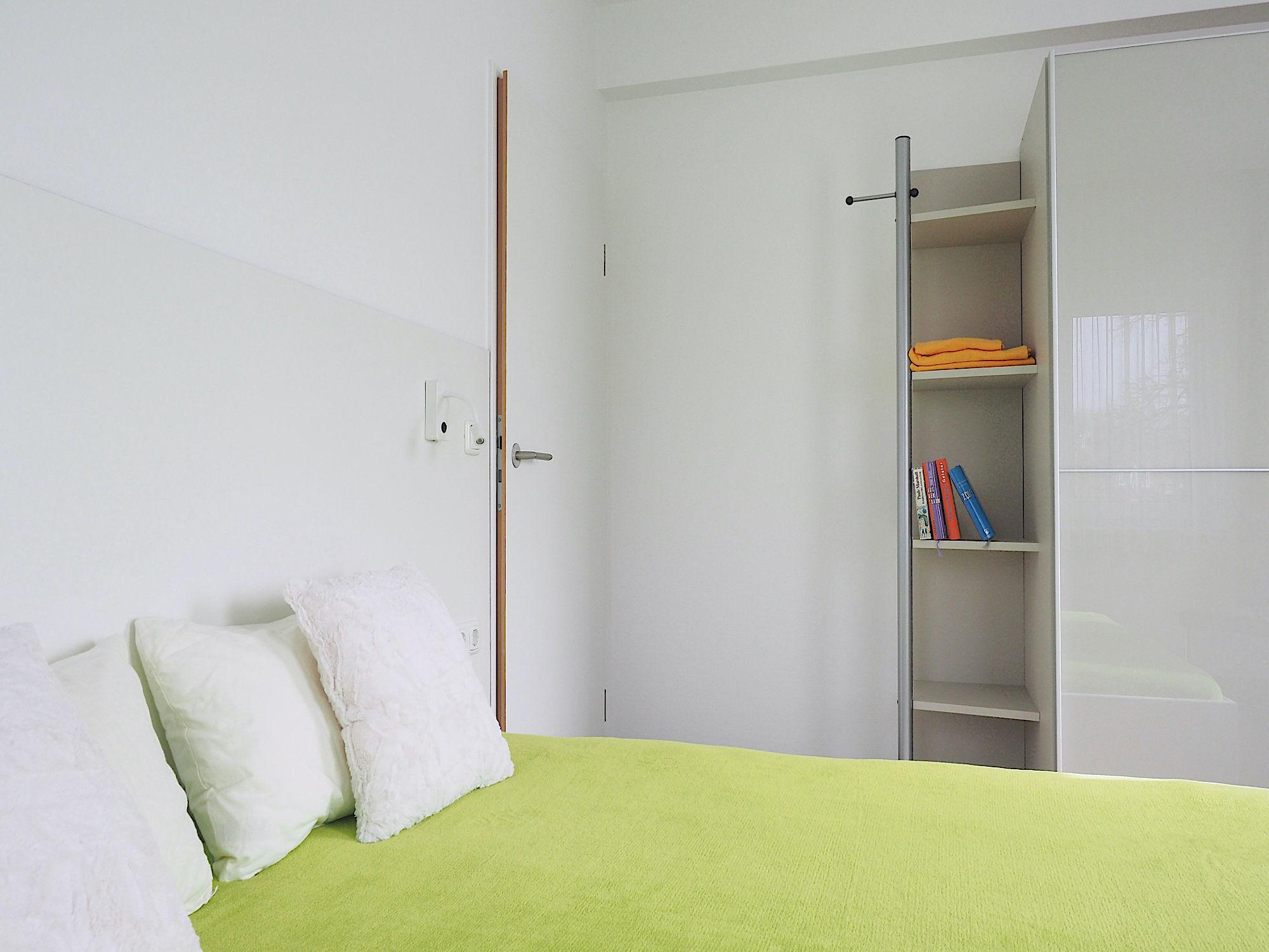 Schlafzimmer mit Doppelbett, im Hintergrund ein großer Kleiderschrank mit Regalteil