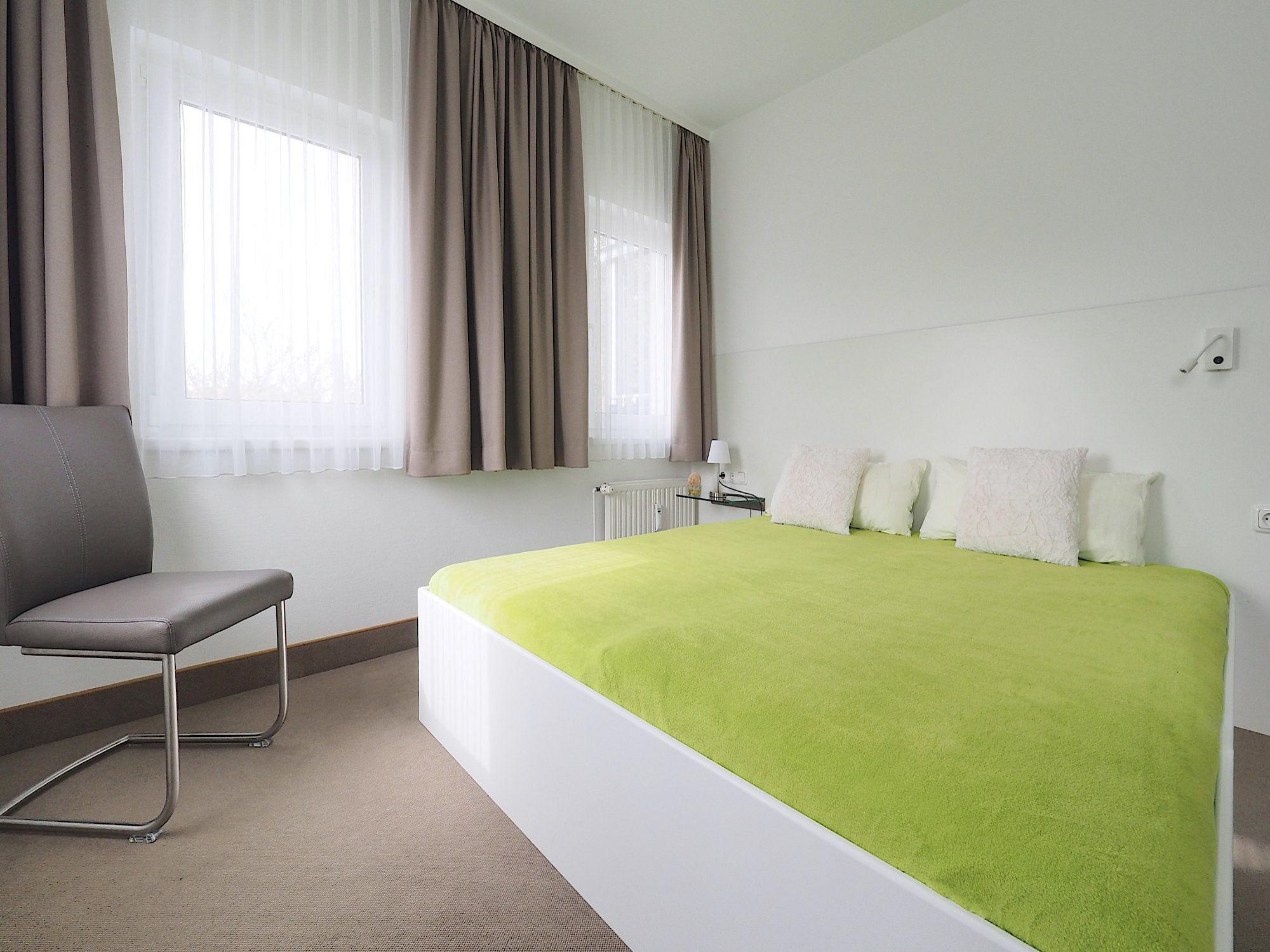 Schlafzimmer mit  Doppelbett, im Hintergrund zwei große Fenster