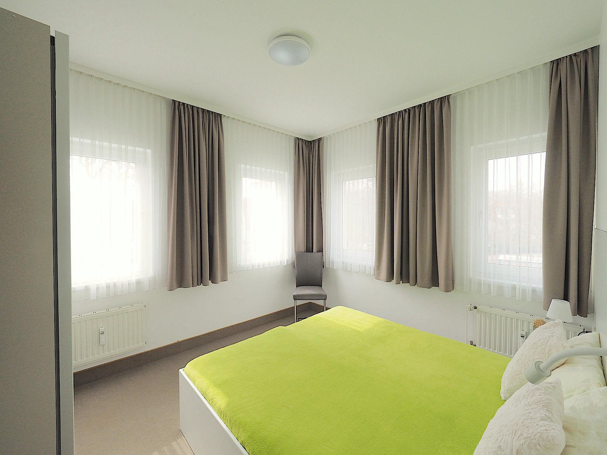 Schlafzimmer mit Doppelbett, dahinter sind an zwei Wänden je 2 Fenster, auf der linken Seite befindet sich ein Kleiderschrank