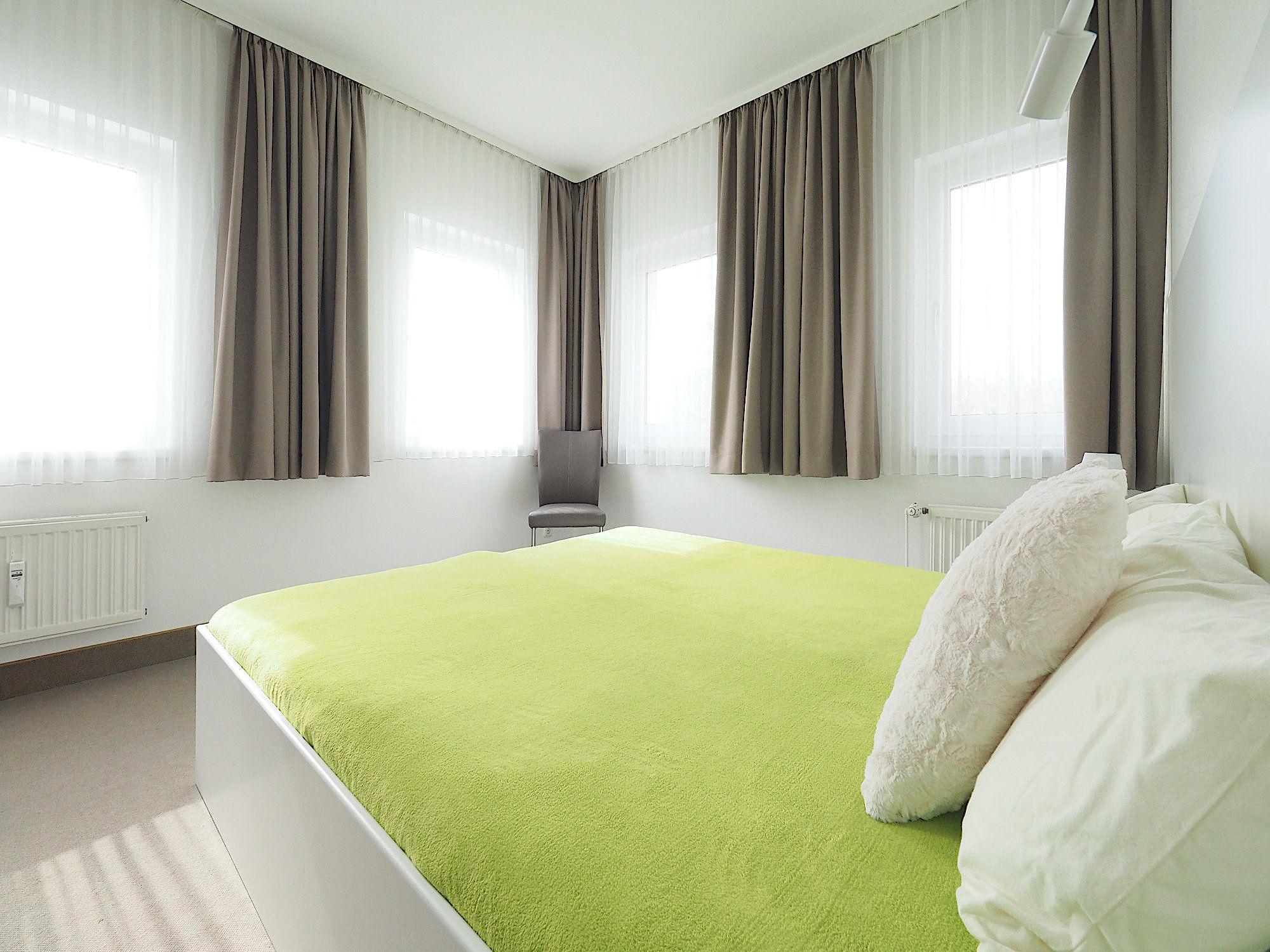 Schlafzimmer mit Doppelbett, dahinter sind an zwei Wänden je 2 Fenster