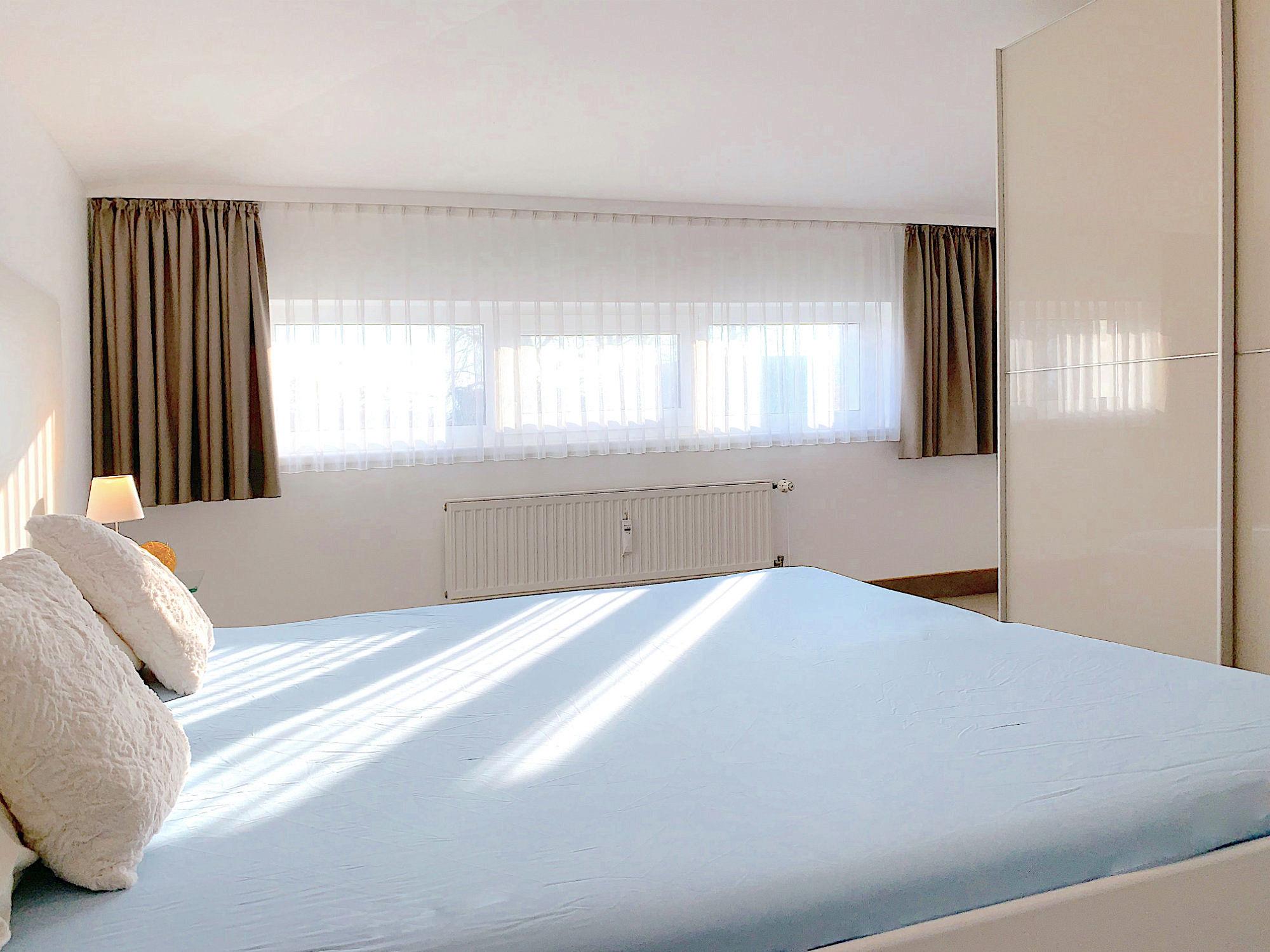 Schlafzimmer mit Doppelbett, dahinter ein langgestrecktes Fenster