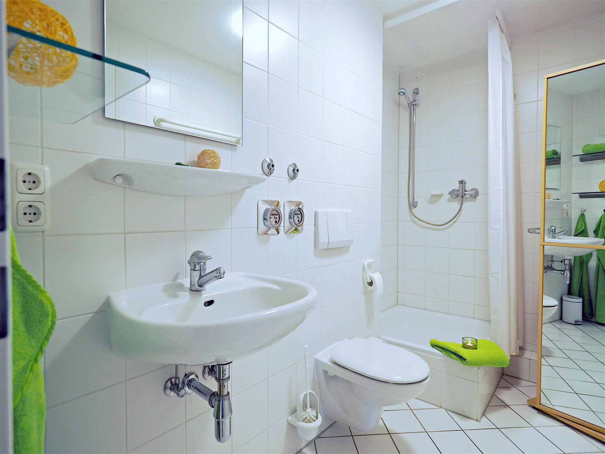 Duschbad mit mit Dusche, links davon ein Waschbecken mit Spiegel, auf der rechten Seite ein Hochschrank mit Spiegelfront