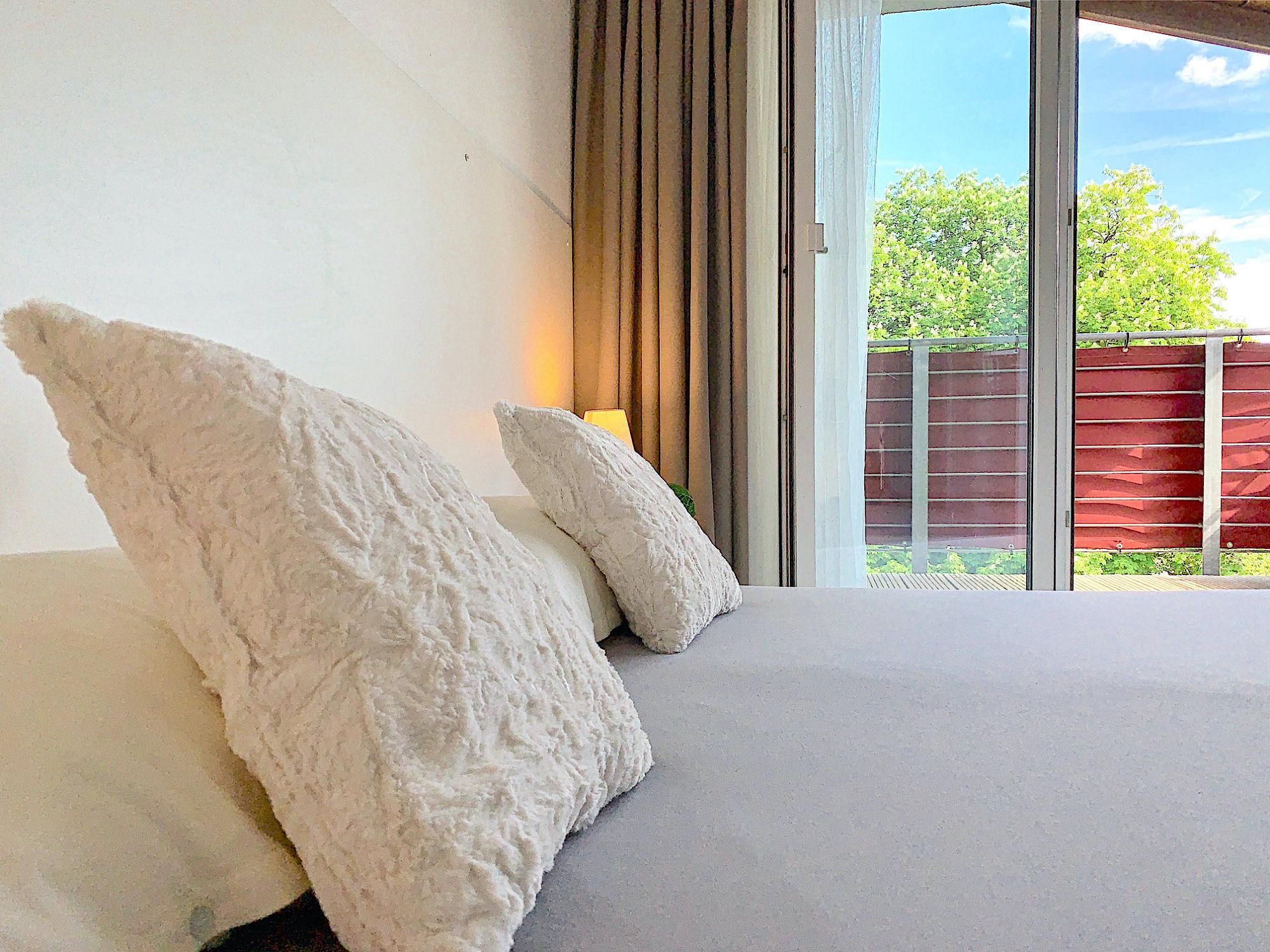 Schlafzimmer mit Doppelbett, Kopfteil mit Kopfkissen, dahinter bodentiefe Fenster mit Balkon