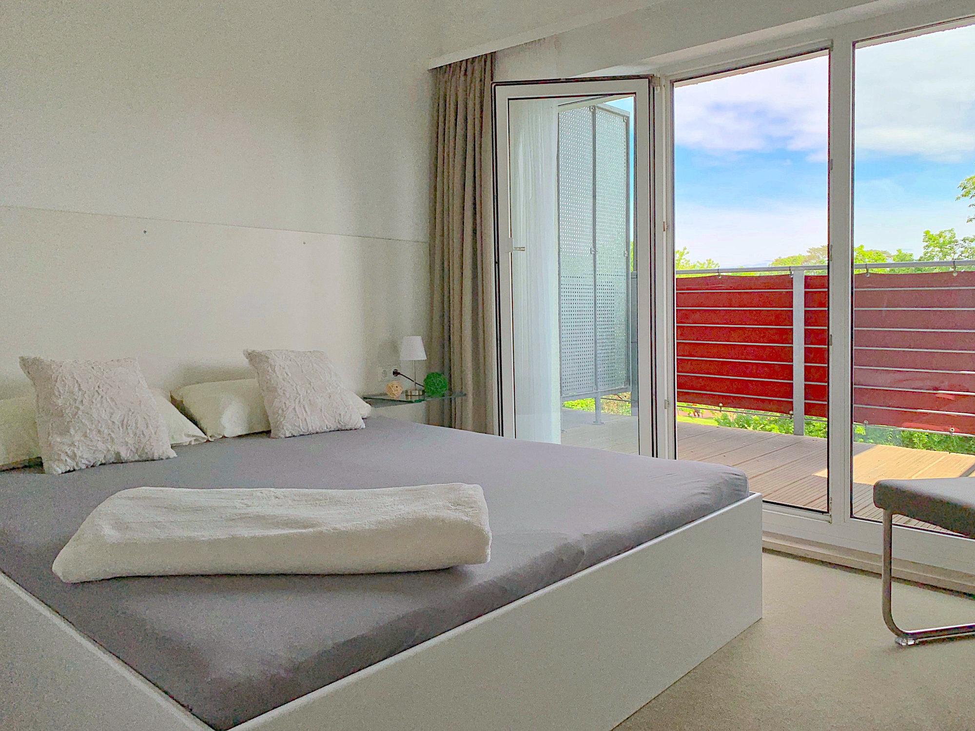 Schlafzimmer mit Doppelbett, dahinter bodentiefe Fenster mit Balkon