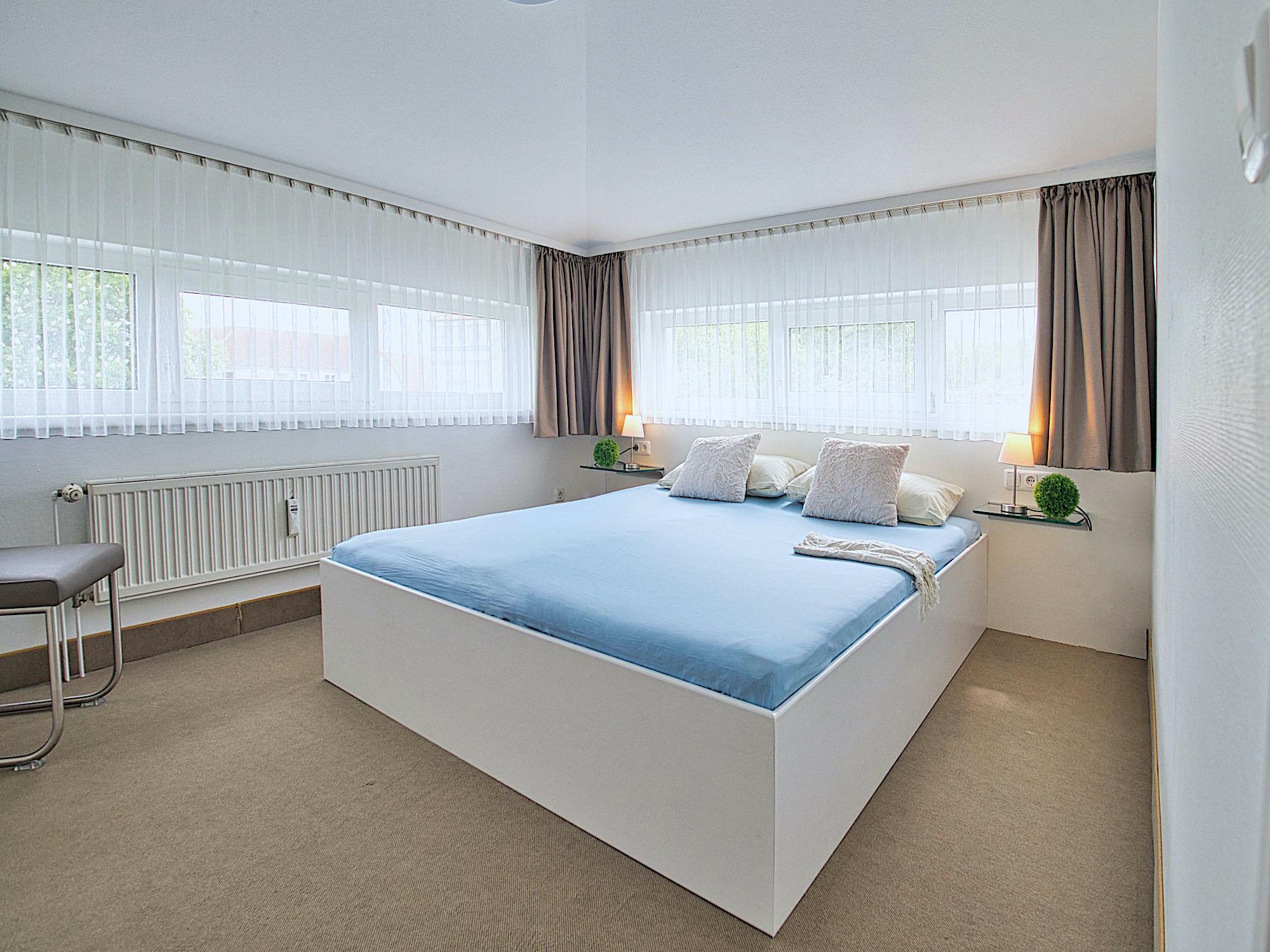 Zweites Schlafzimmer mit Doppelbett, breite Fensterfronten an zwei Wänden