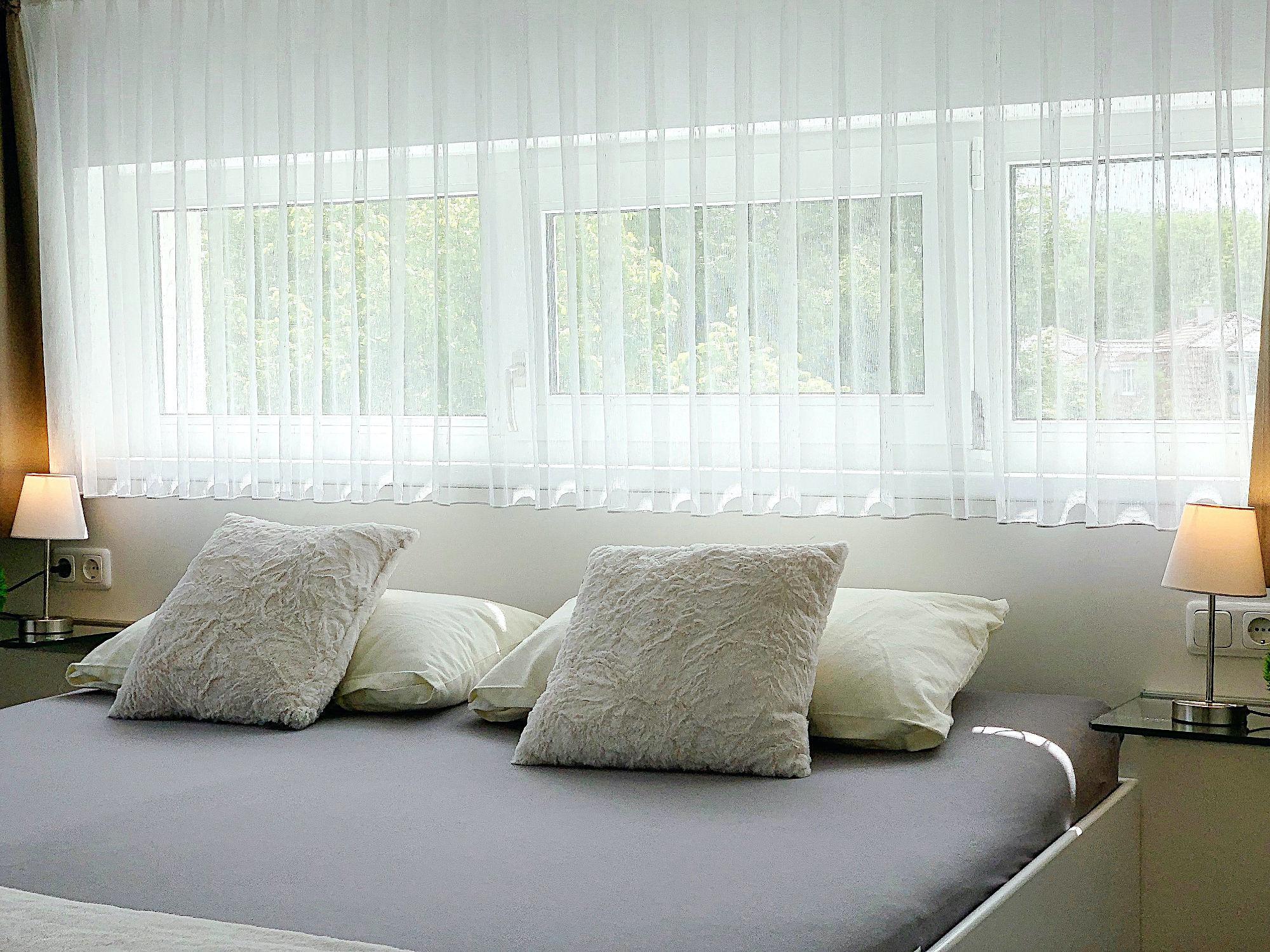 Zweites Schlafzimmer mit Doppelbett, Kopfteil mit Kopfkissen, dahinter ein breites Fenster