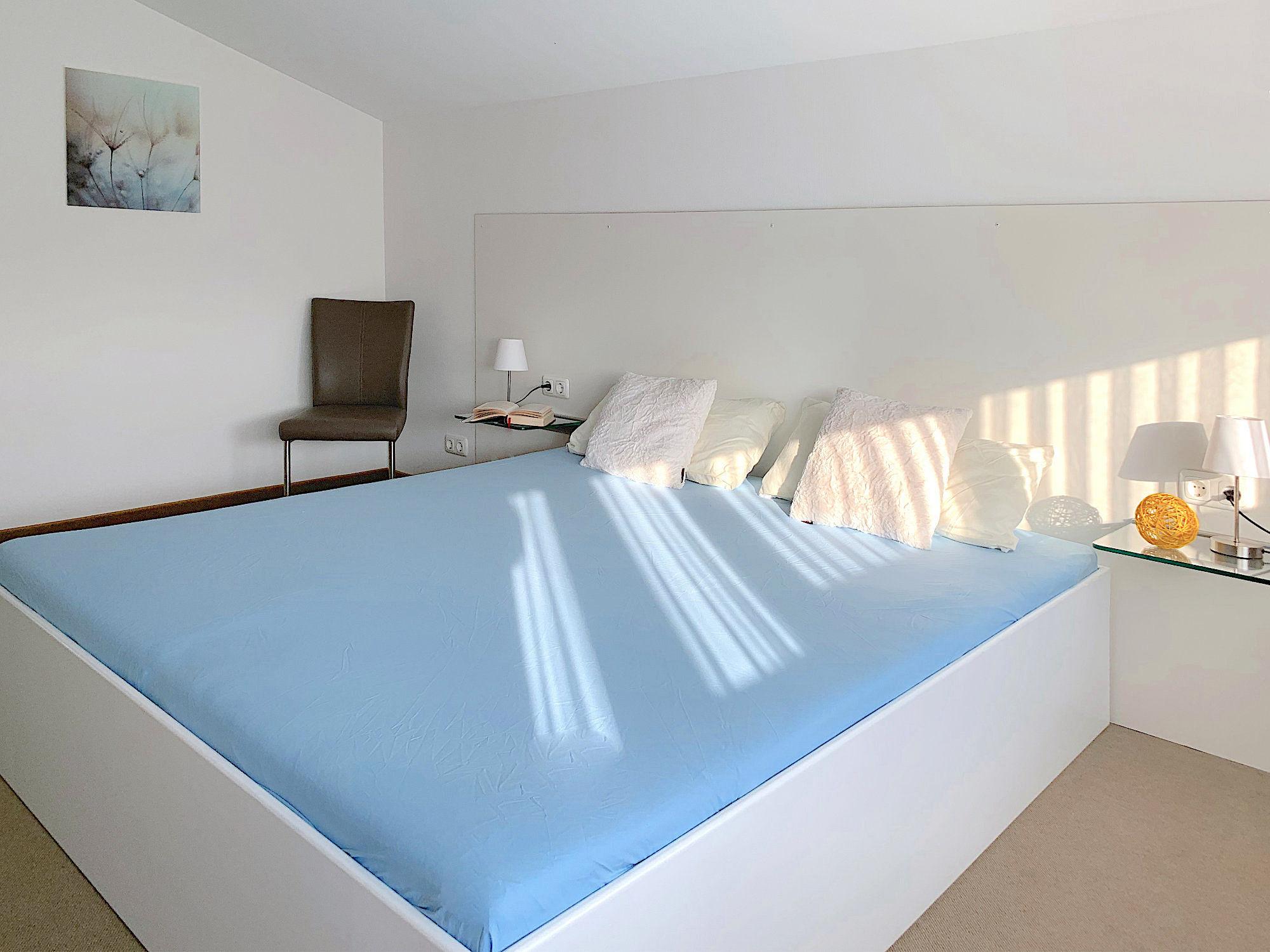 Schlafzimmer mit Doppelbett, dahinter ein Stuhl