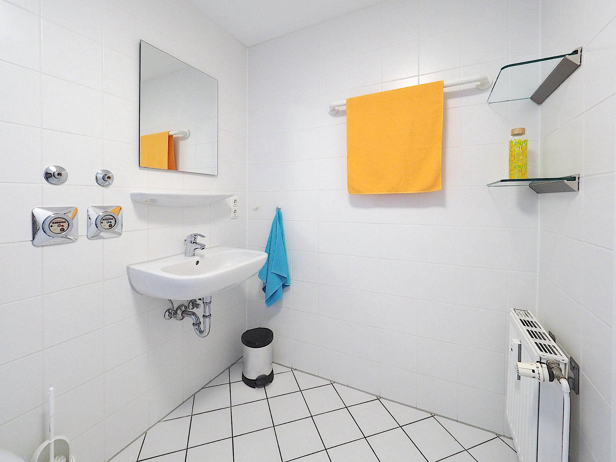 Duschbad mit Waschbecken, Spiegel  und Regalen