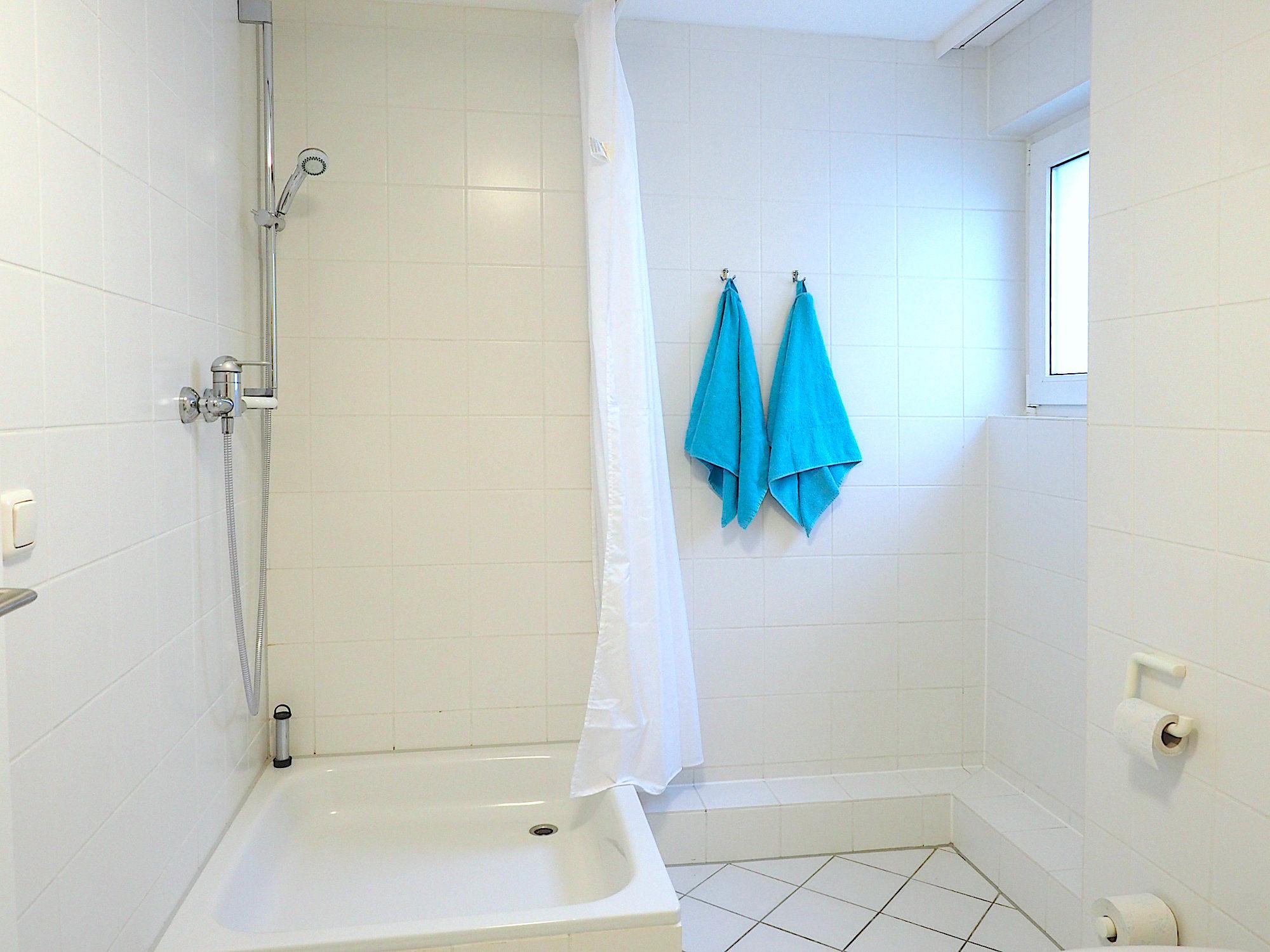 Duschbad mit Dusche, rechts davon ein Fenster