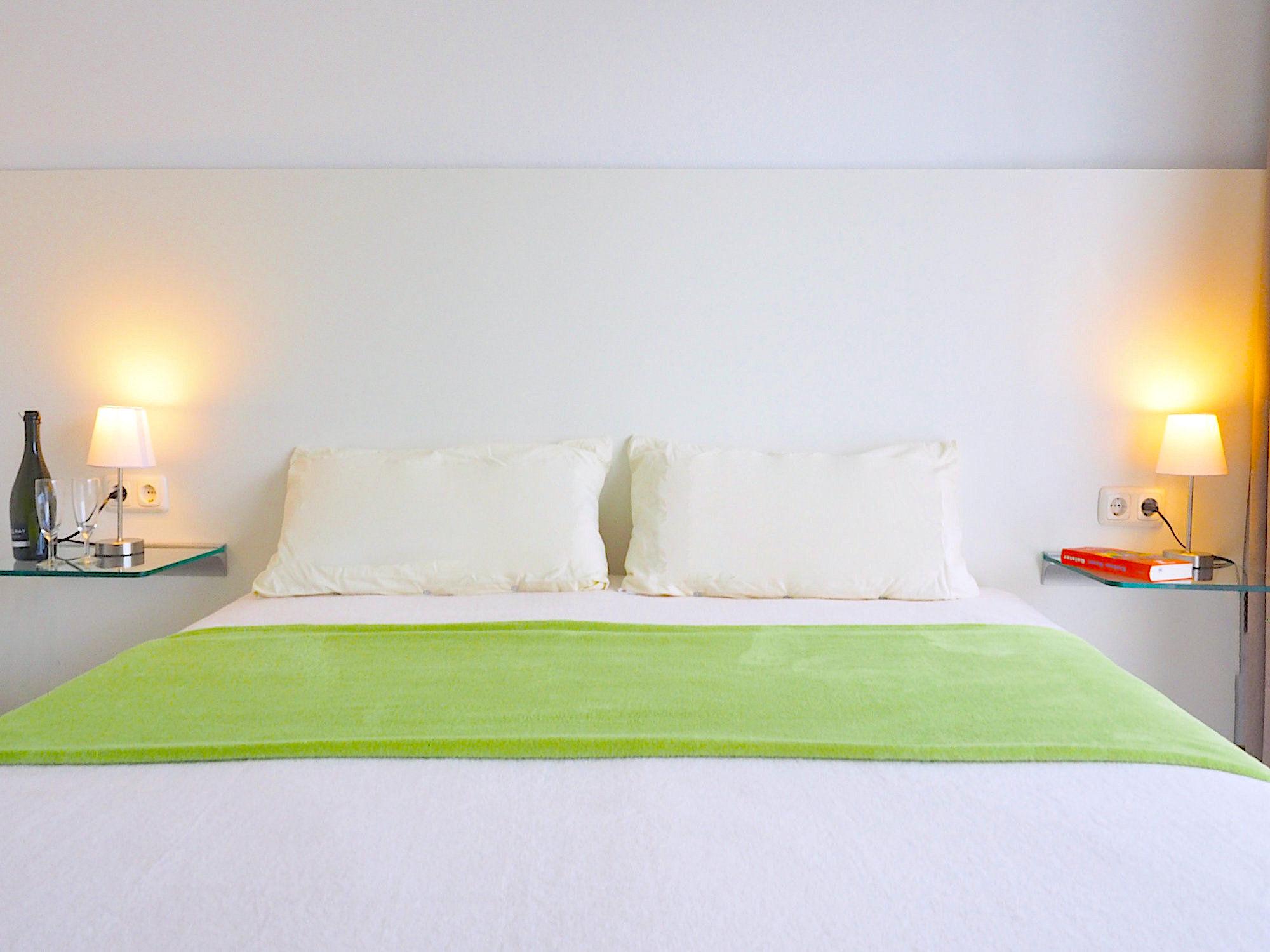 Schlafzimmer mit Doppelbett, Kopfteil mit Kopfkissen, Glaskonsolen links und rechts vom Bett