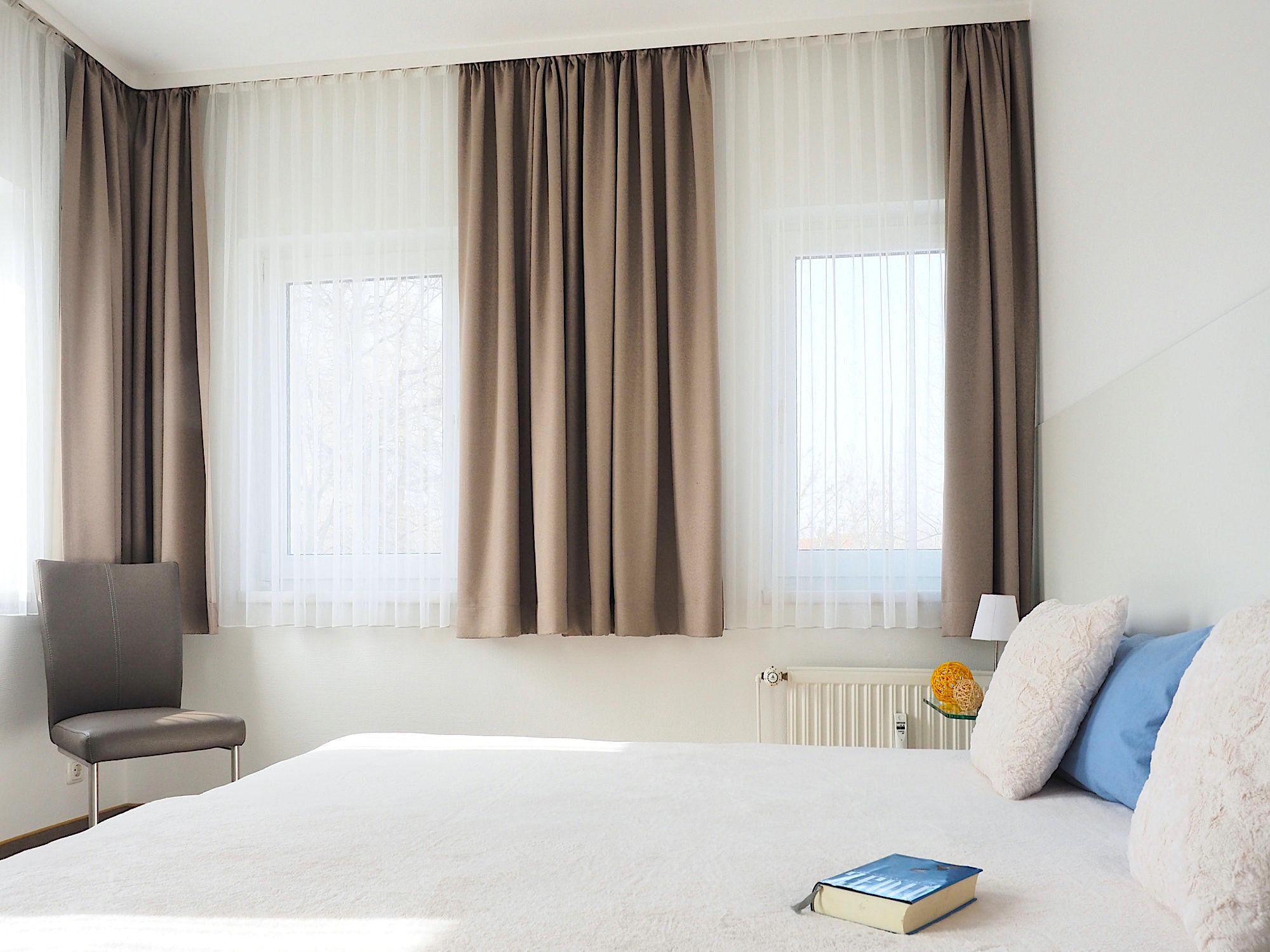 Zweites Schlafzimmer mit Doppelbett, dahinter zwei Fenster mit Vorhängen