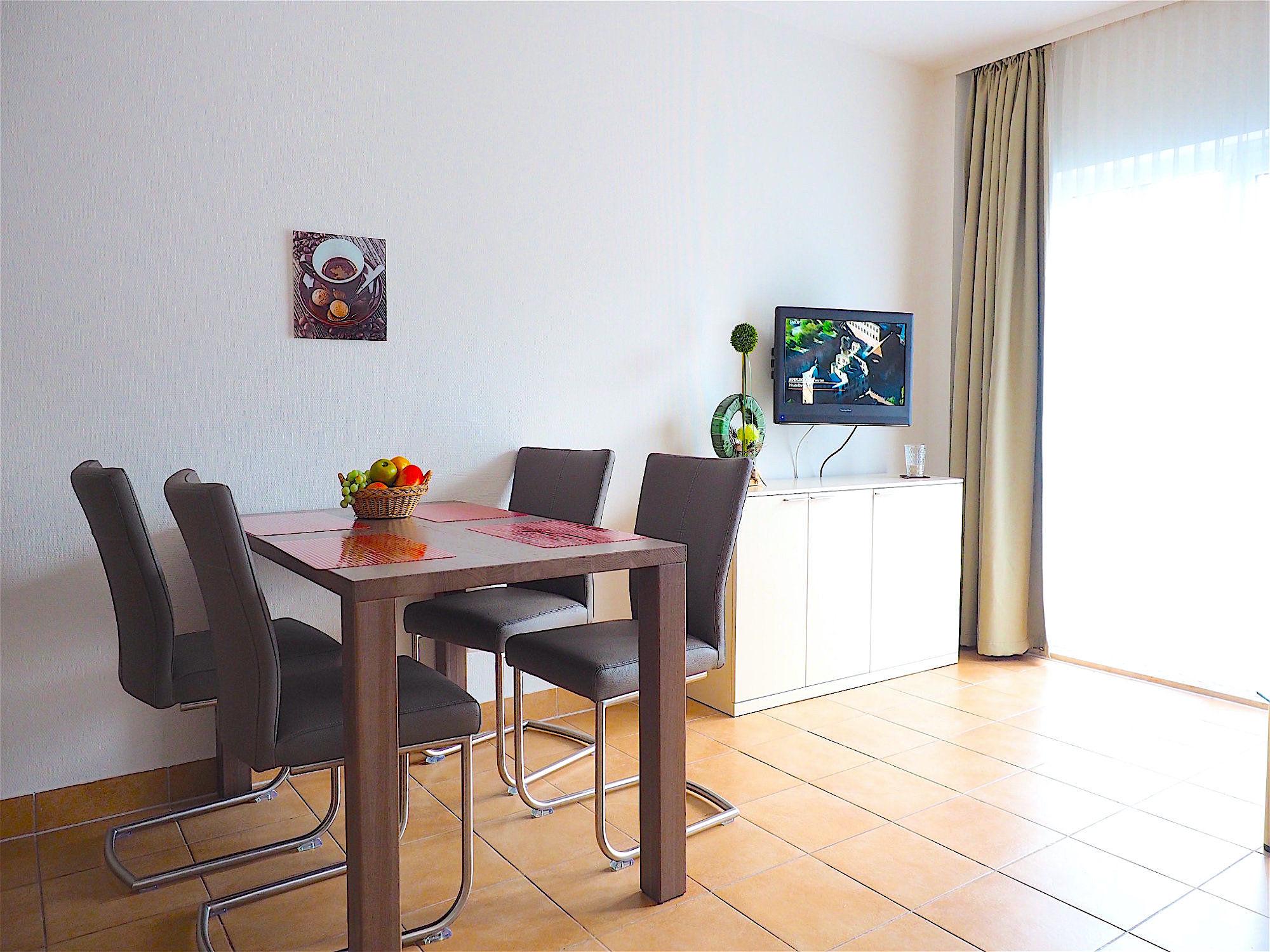 Esstisch mit vier Stühlen, daneben steht ein Sideboard mit Flatscreen TV, rechts davon befinden sich bodentiefe Fenster