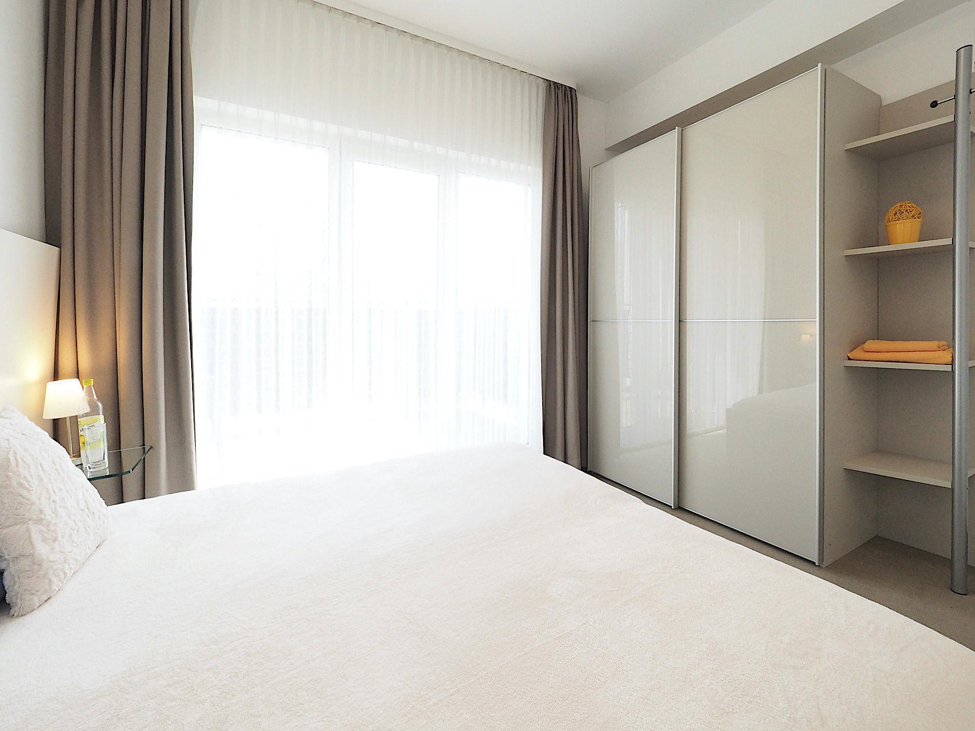 Schlafzimmer mit Doppelbett, rechts davon großer Kleiderschrank mit Regalteil, im Hintergrund bodentiefe Fenster