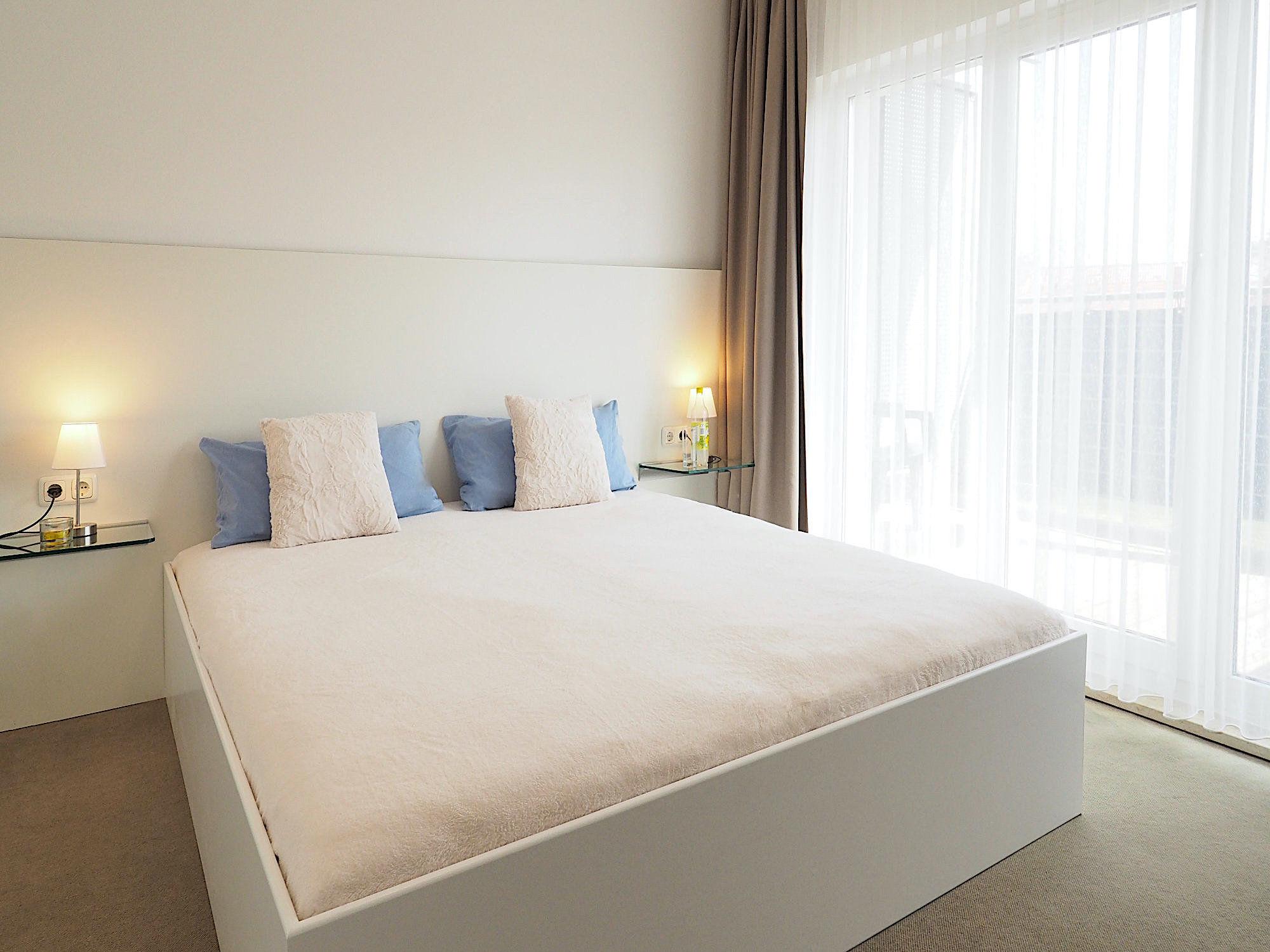 Schlafzimmer mit Doppelbett, an jeder Seite sind Glaskonsolen, rechts von dem Bett befinden sich bodentiefe Fenster