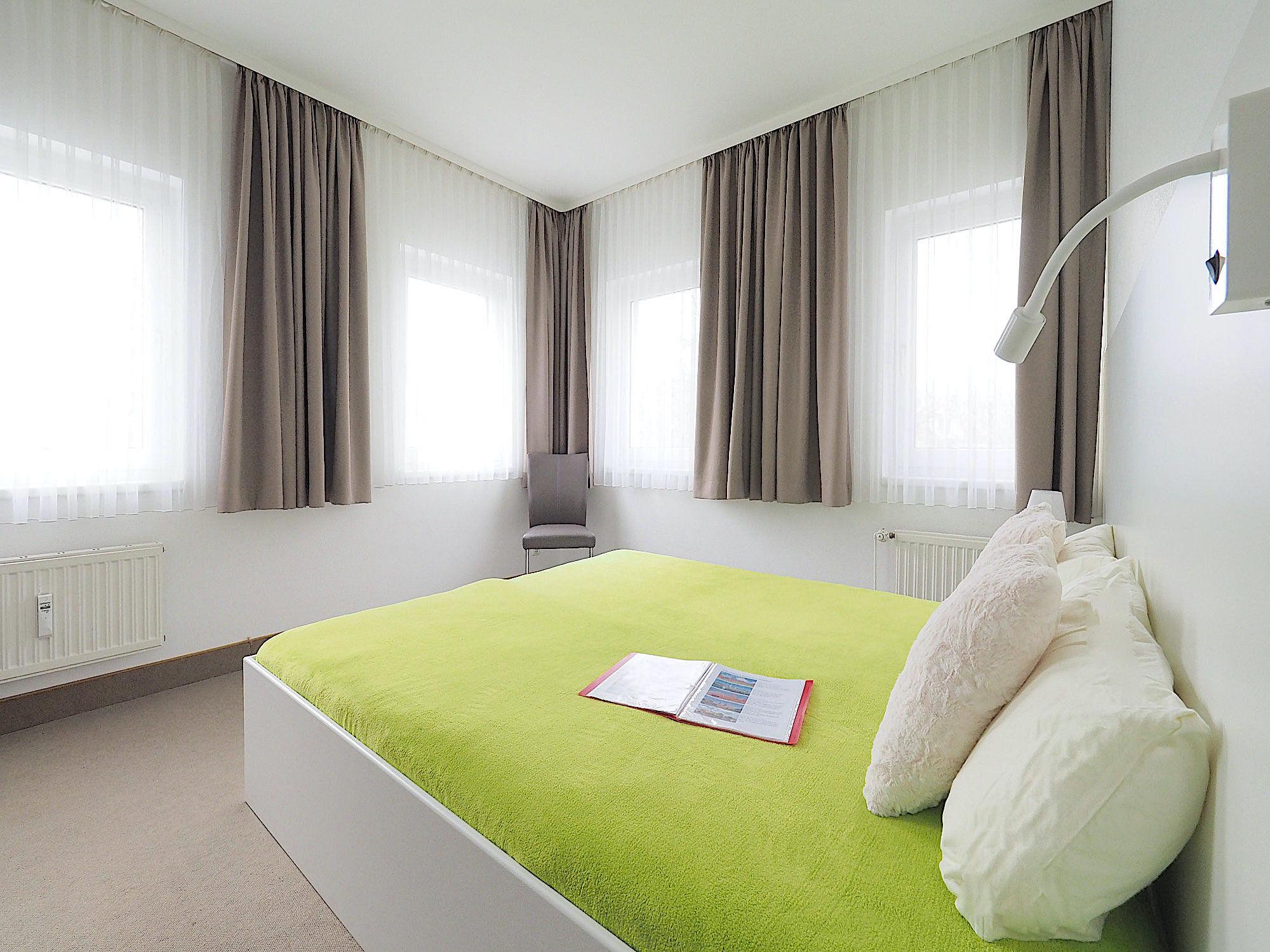 Zweites Schlafzimmer mit Doppelbett, an zwei Wänden jeweils 2 Fenster