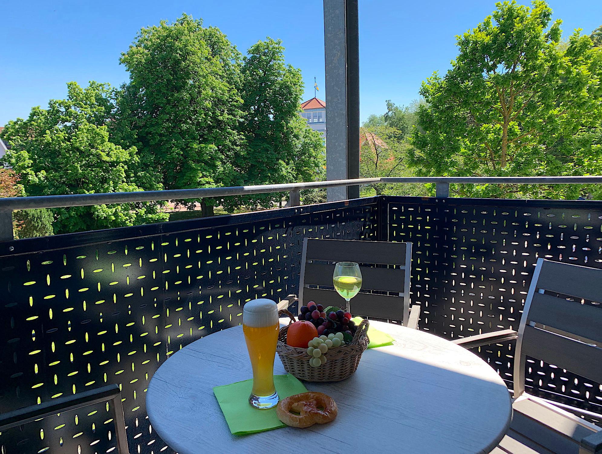 Balkon mit Tisch und Stühlen, Blick ins Grüne und zum Kurhaus
