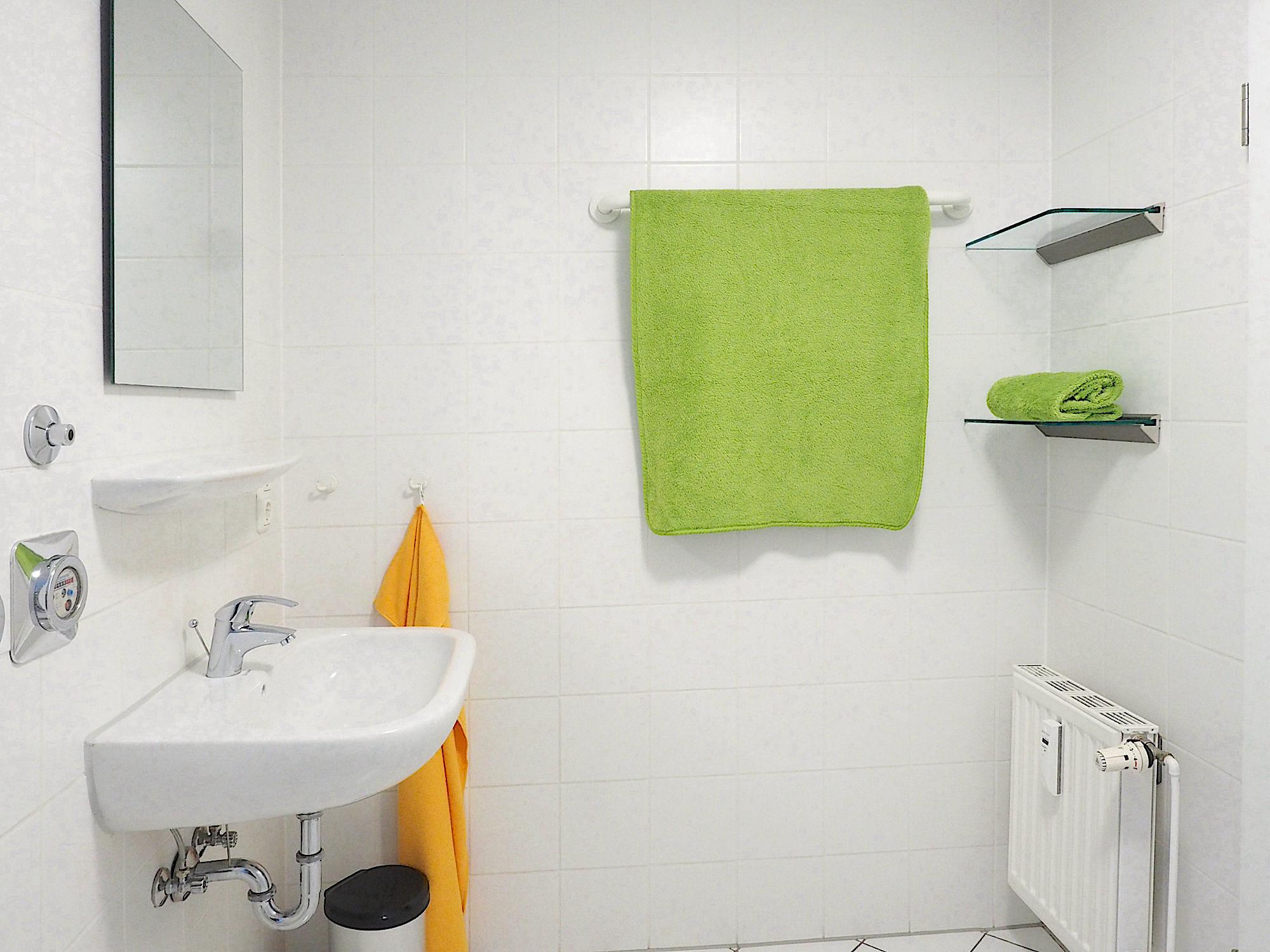 Duschbad mit Waschbecken und Regal