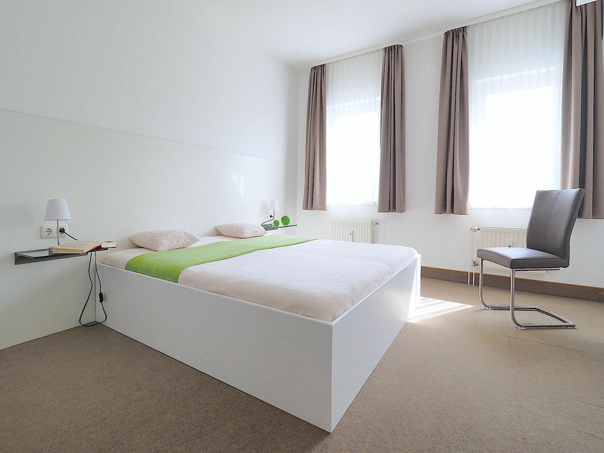 Schlafzimmer mit Doppelbett, rechts davon zwei große Fenster