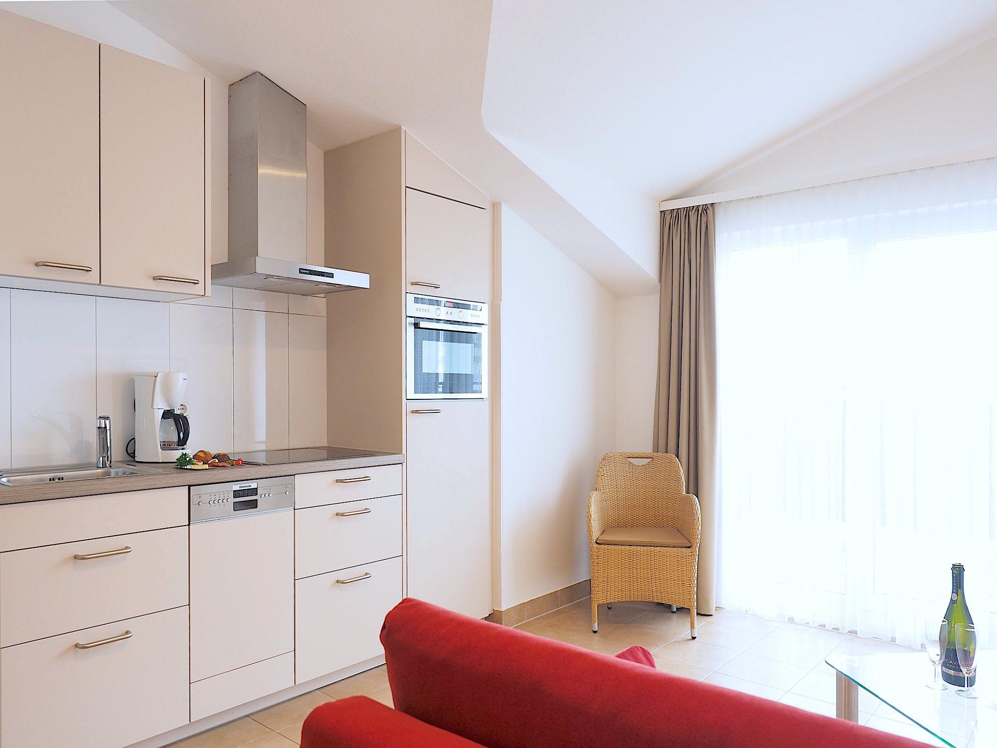 Moderne Küchenzeile mit elektrischen Geräten, rechts davon bodentiefe Fenster zum Balkon