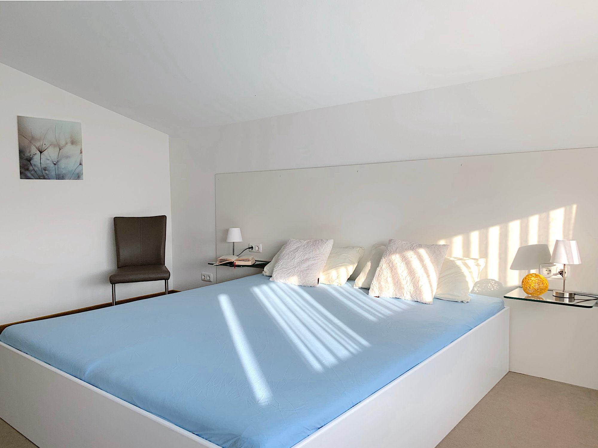 Schlafzimmer mit Doppelbett, dahinter befindet sich ein Stuhl