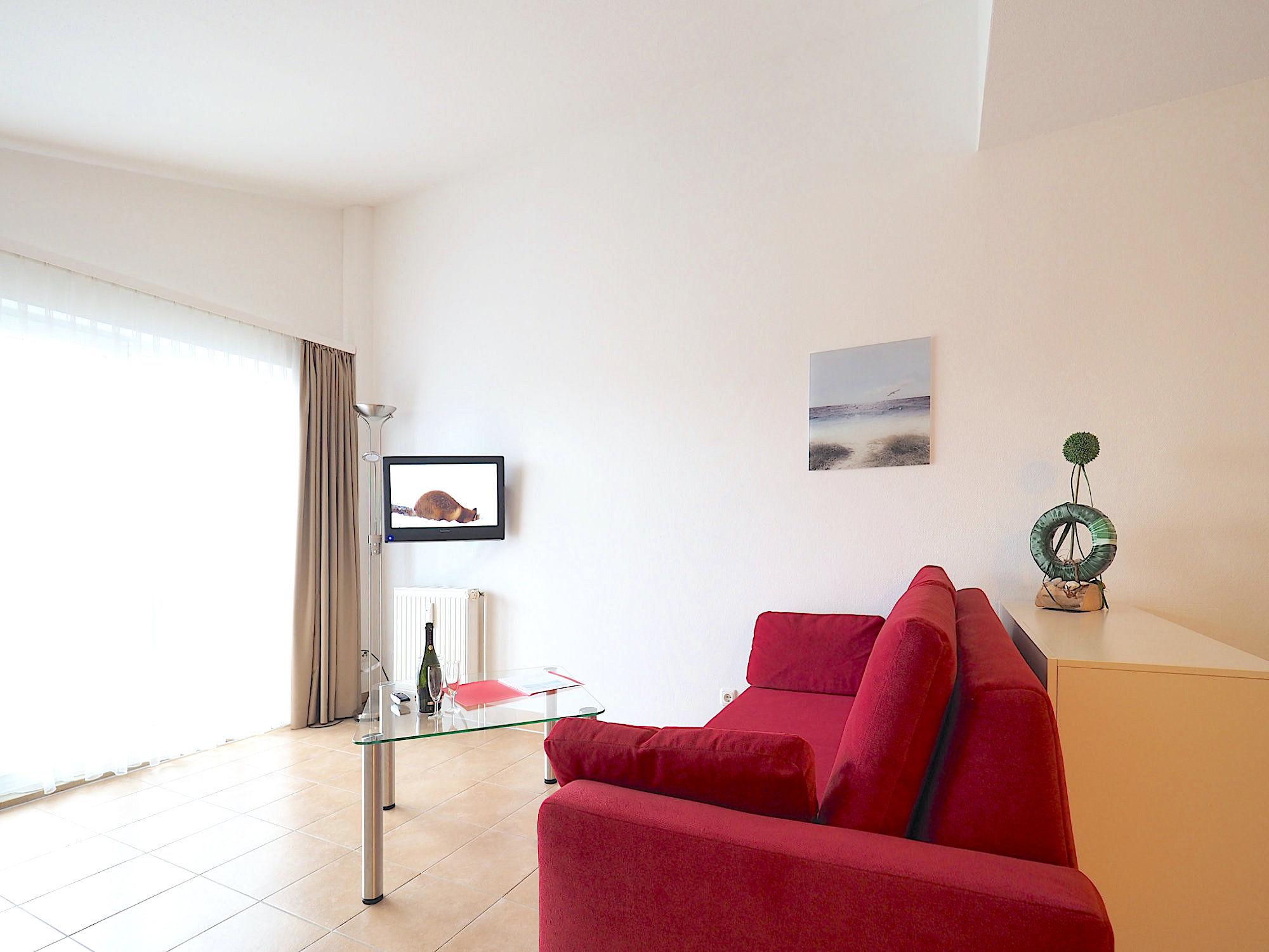 Wohnzimmer mit Couch, Glastisch und Flatsreen TV, im Hintergrund große, bodentiefe Fenster