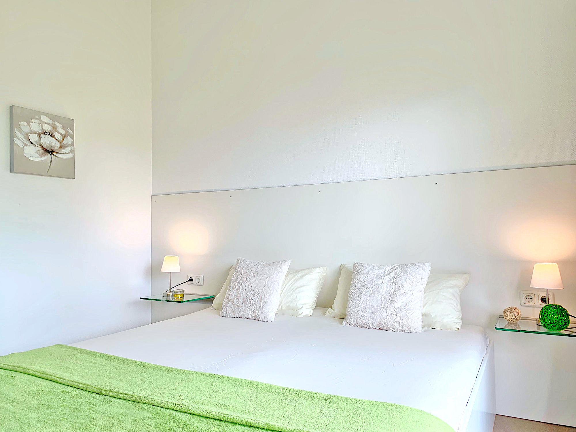 Schlafzimmer mit Doppelbett, Kopfteil mit Kopfkissen, links und rechts neben dem Bett befinden sich Glaskonsolen