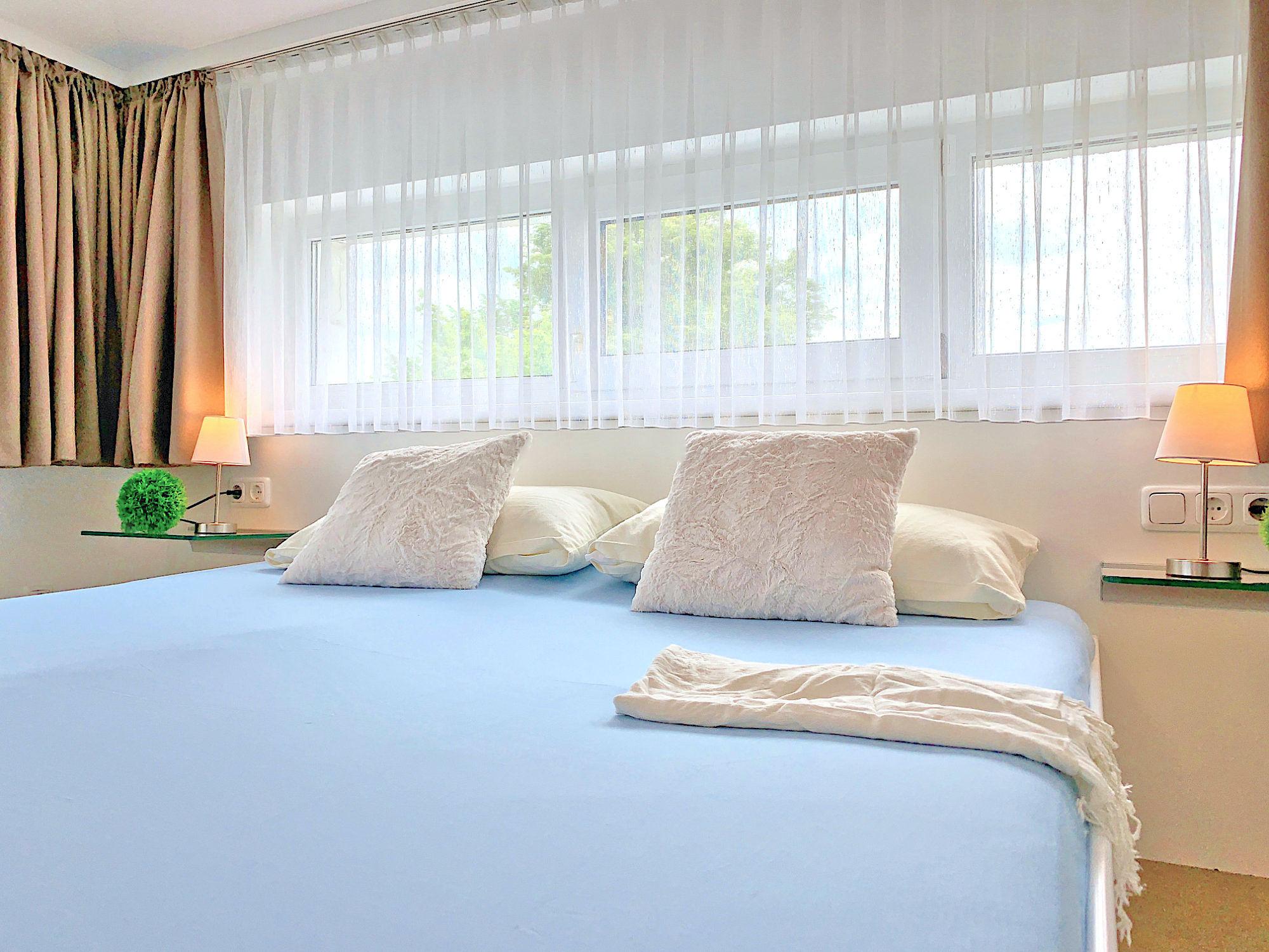 Zweites Schlafzimmer mit Doppelbett, Kopfteil mit Kopfkissen, dahinter eine breite Fensterfront