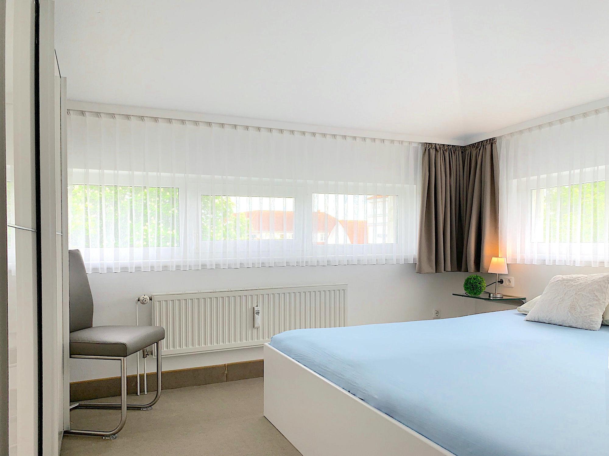 Zweites Schlafzimmer mit Doppelbett, große Fenster an zwei Wänden