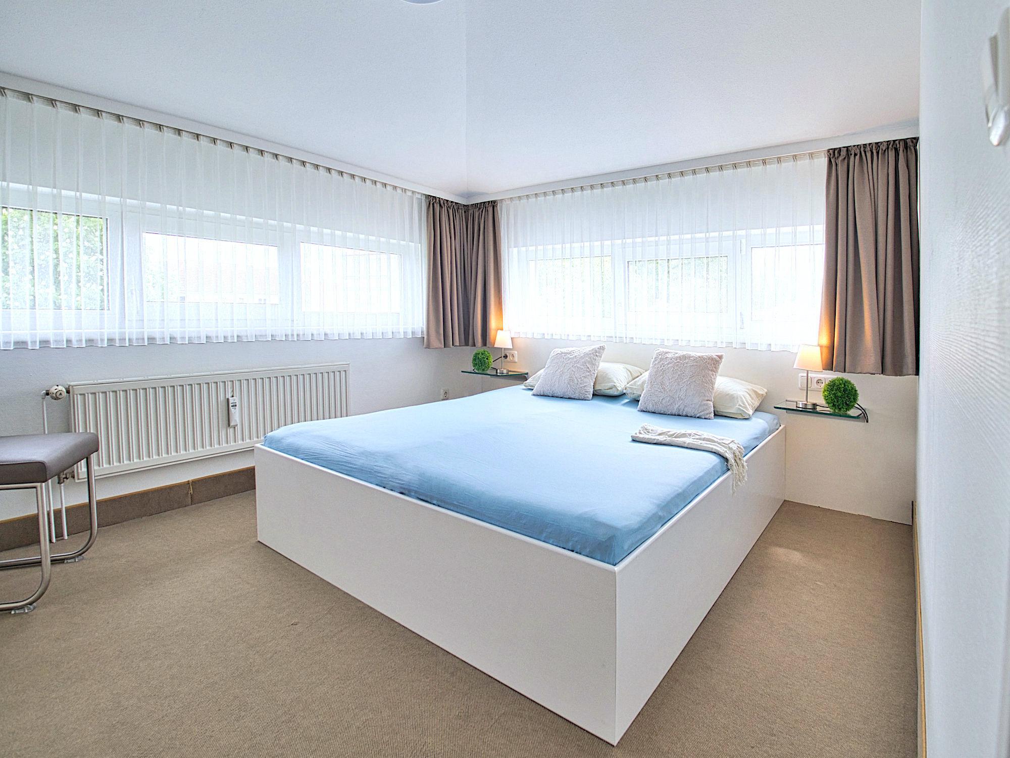 Zweites Schlafzimmer mit Doppelbett, große Fenster an zwei Wänden dahinter
