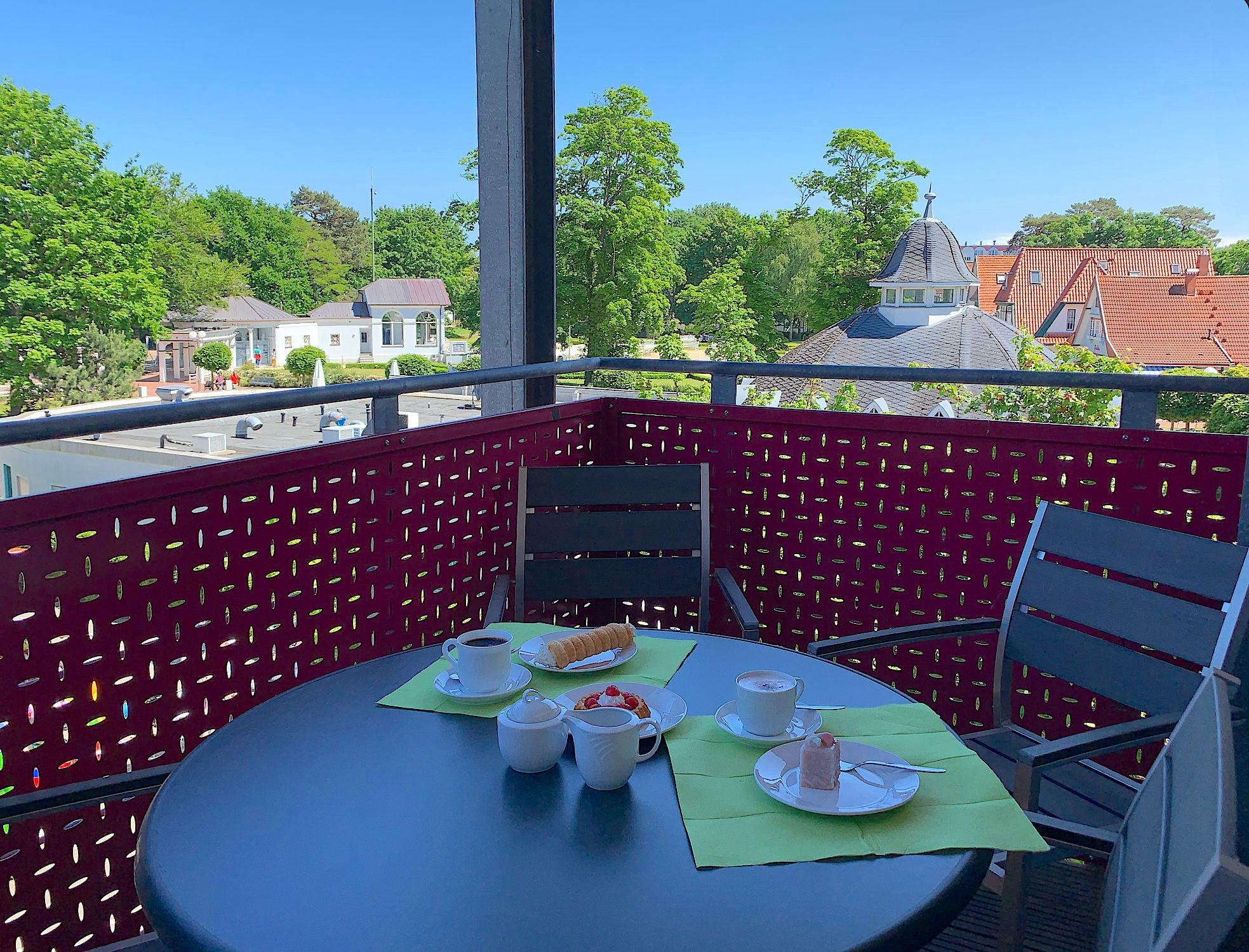 Balkon mit Tisch und Stühlen, Blick in den Kurpark