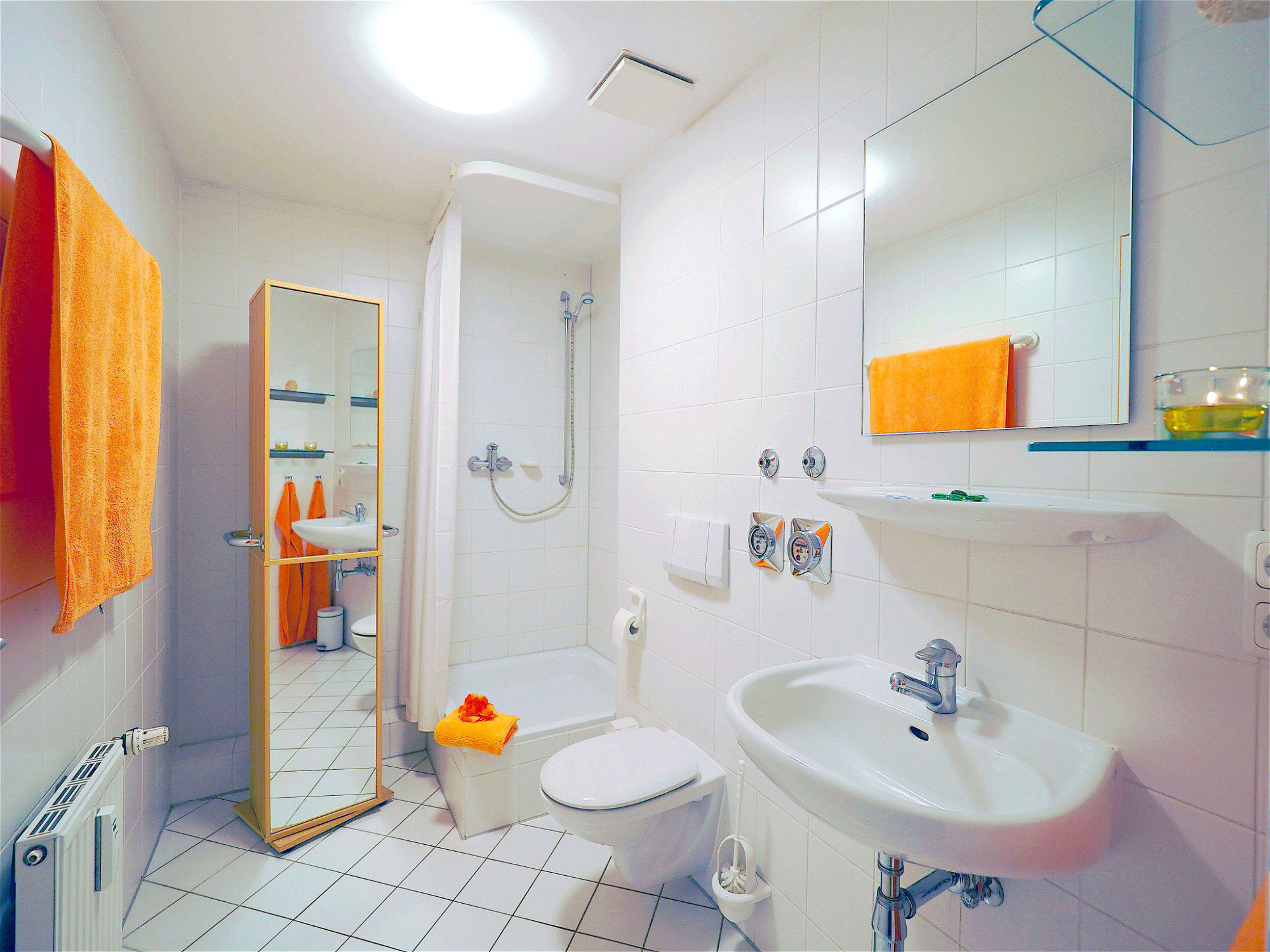 Duschbad mit mit Dusche, rechts davon ein Waschbecken mit Spiegel, auf der linken Seite ein Hochschrank mit Spiegelfront