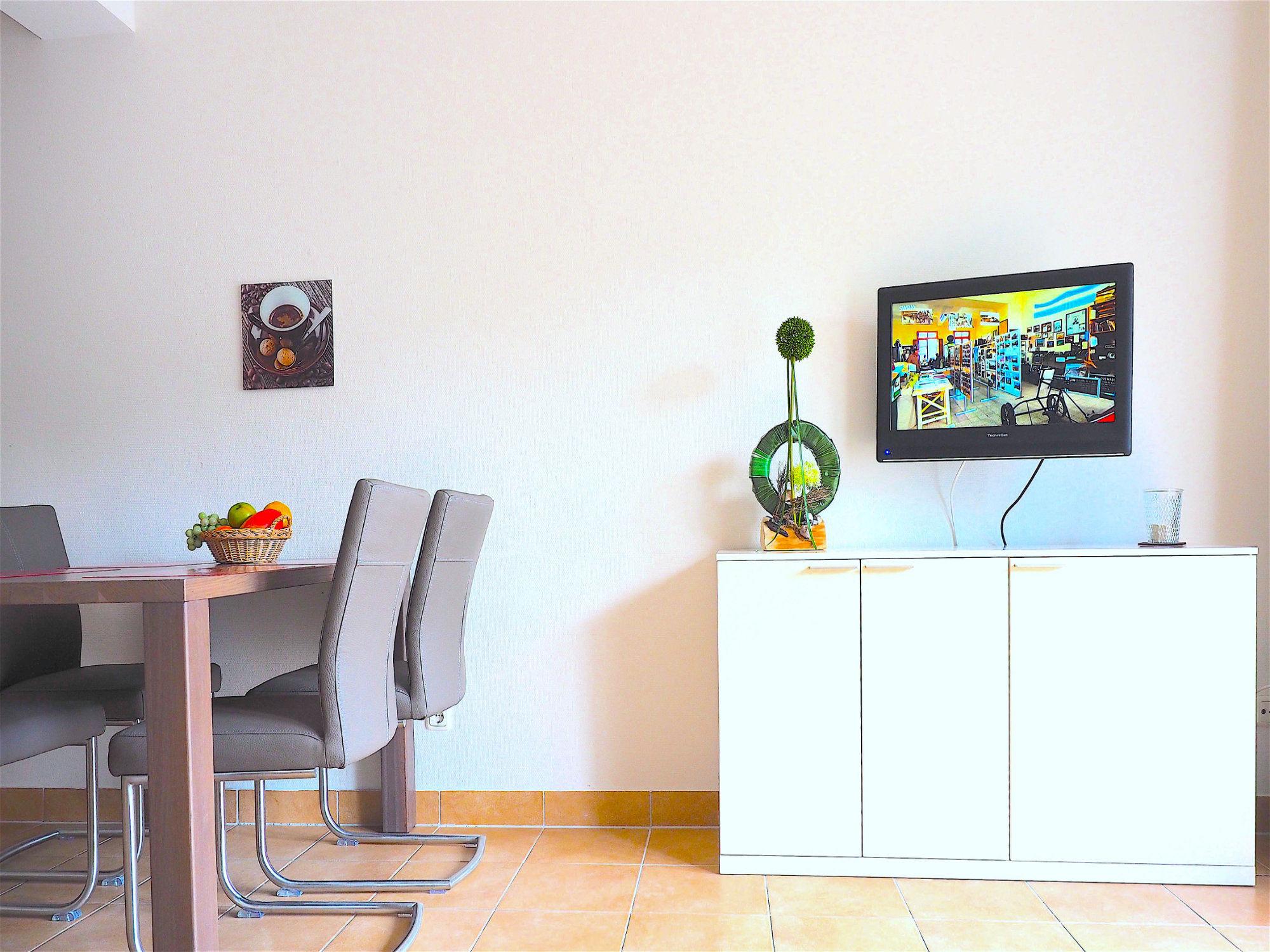 Wohnzimmer, links der Esstisch mit Stühlen, rechts ein Sideboard mit Flatscreen TV und Deko