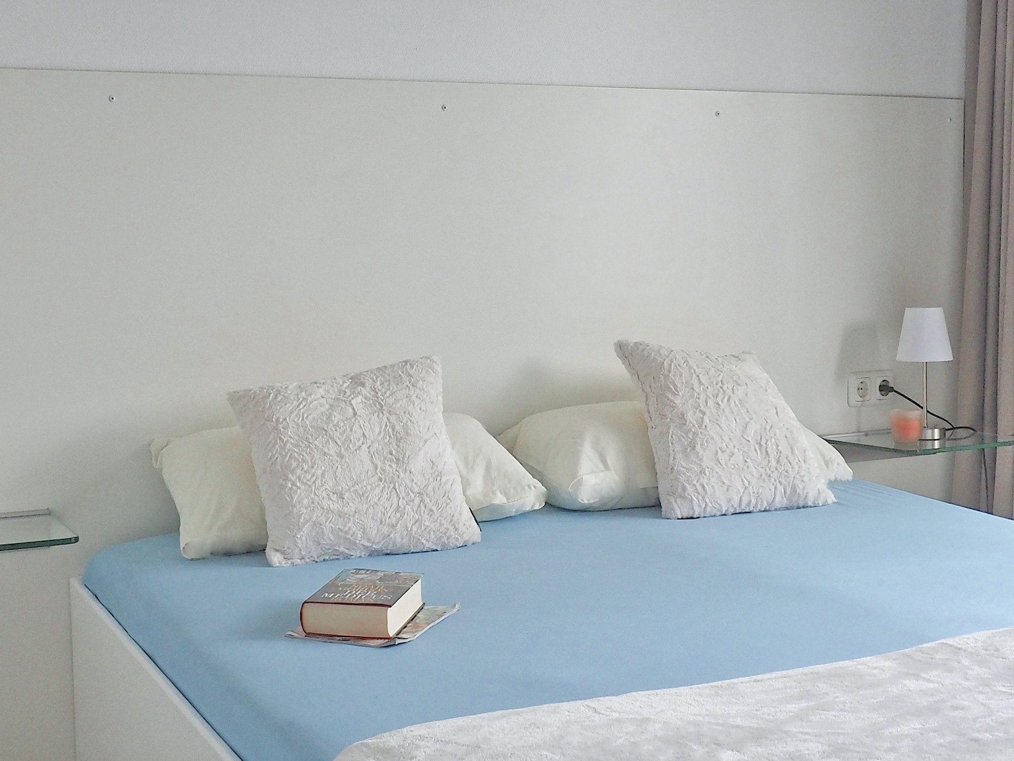 Schlafzimmer mit Doppelbett, Kopfteil mit Kopfkissen, Glaskonsolen links und rechts von dem Bett