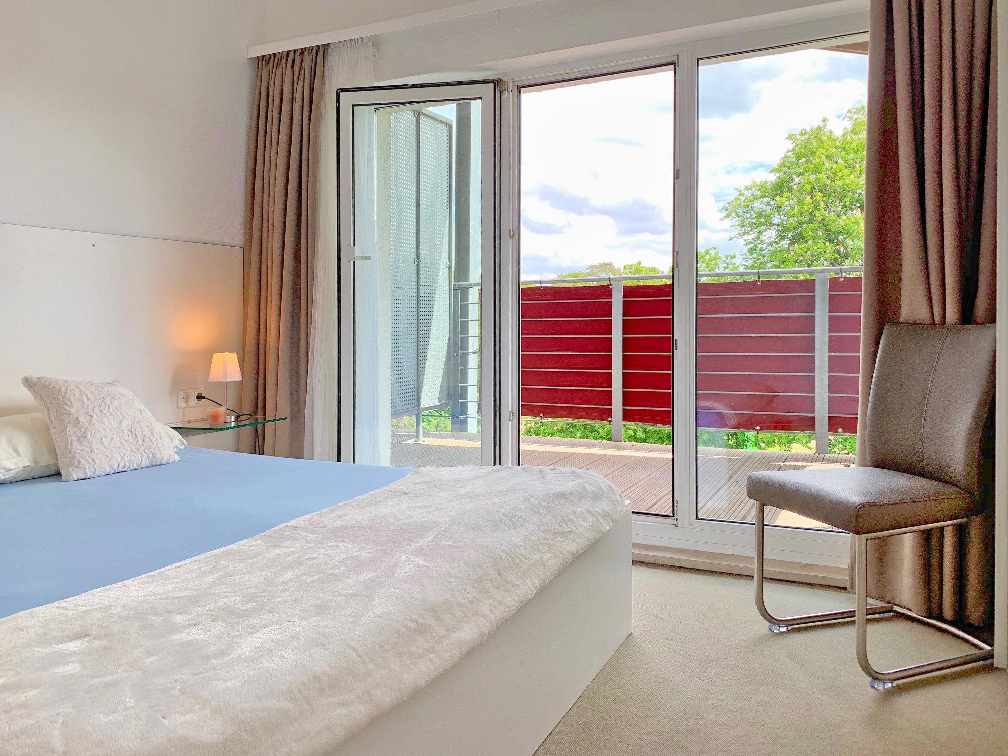 Schlafzimmer mit Doppelbett, rechts davon bodentiefe Fenster und Zugang zum Balkon