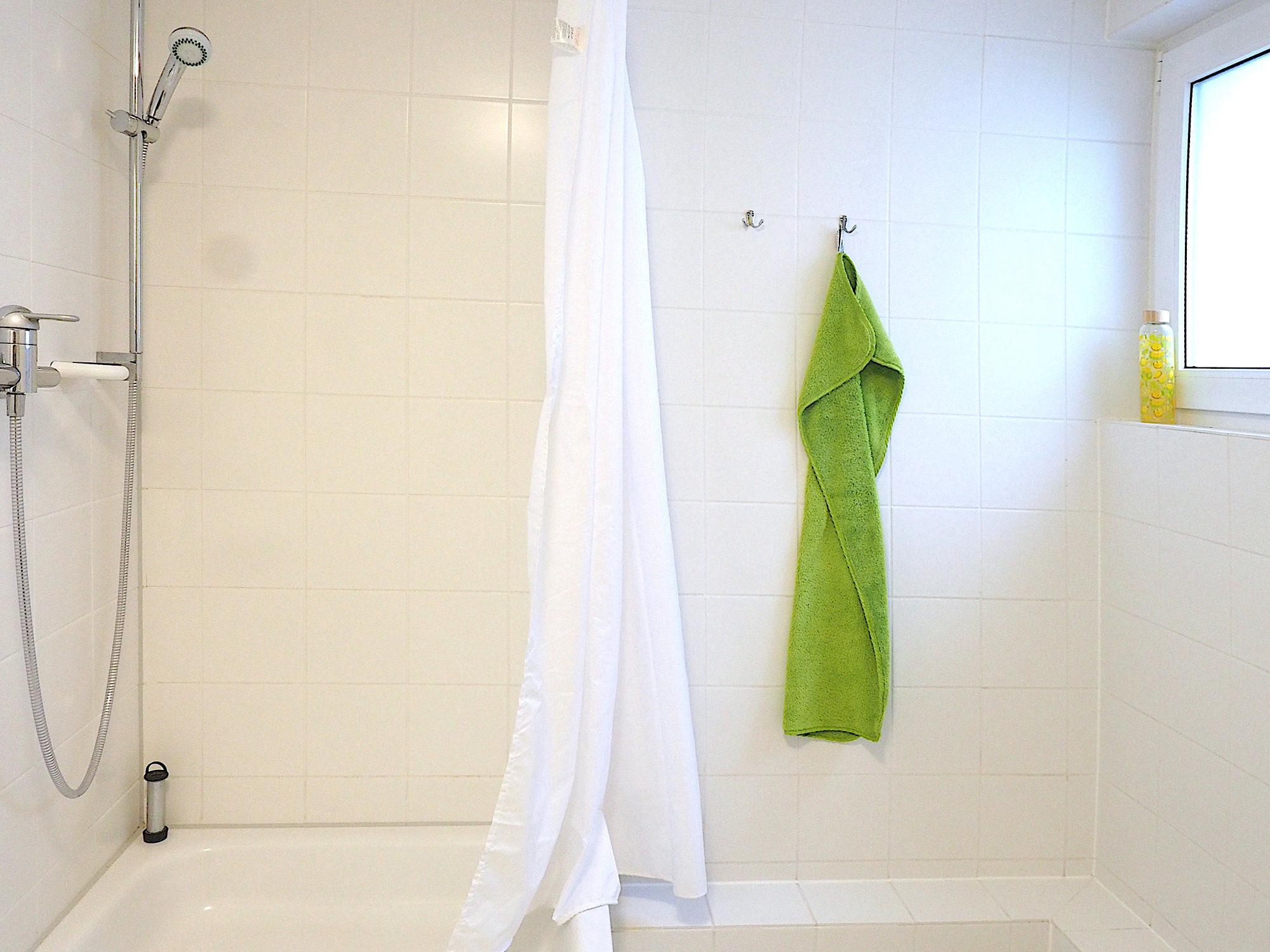 Duschbad, links ist eine Dusche, rechts davon ein Fenster