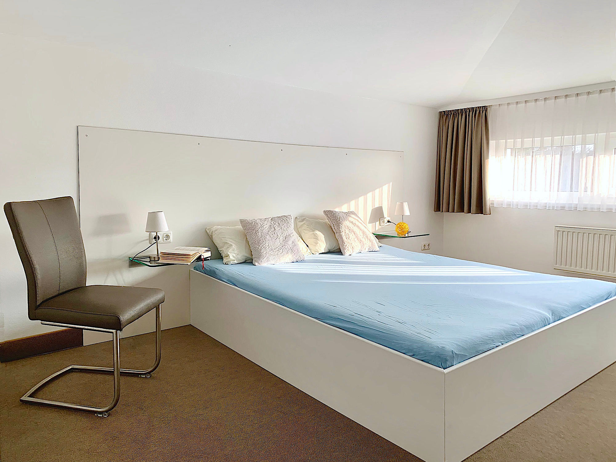 Schlafzimmer mit Doppelbett,  dahinter ein breites Fenster. Links im Bild ein Stuhl