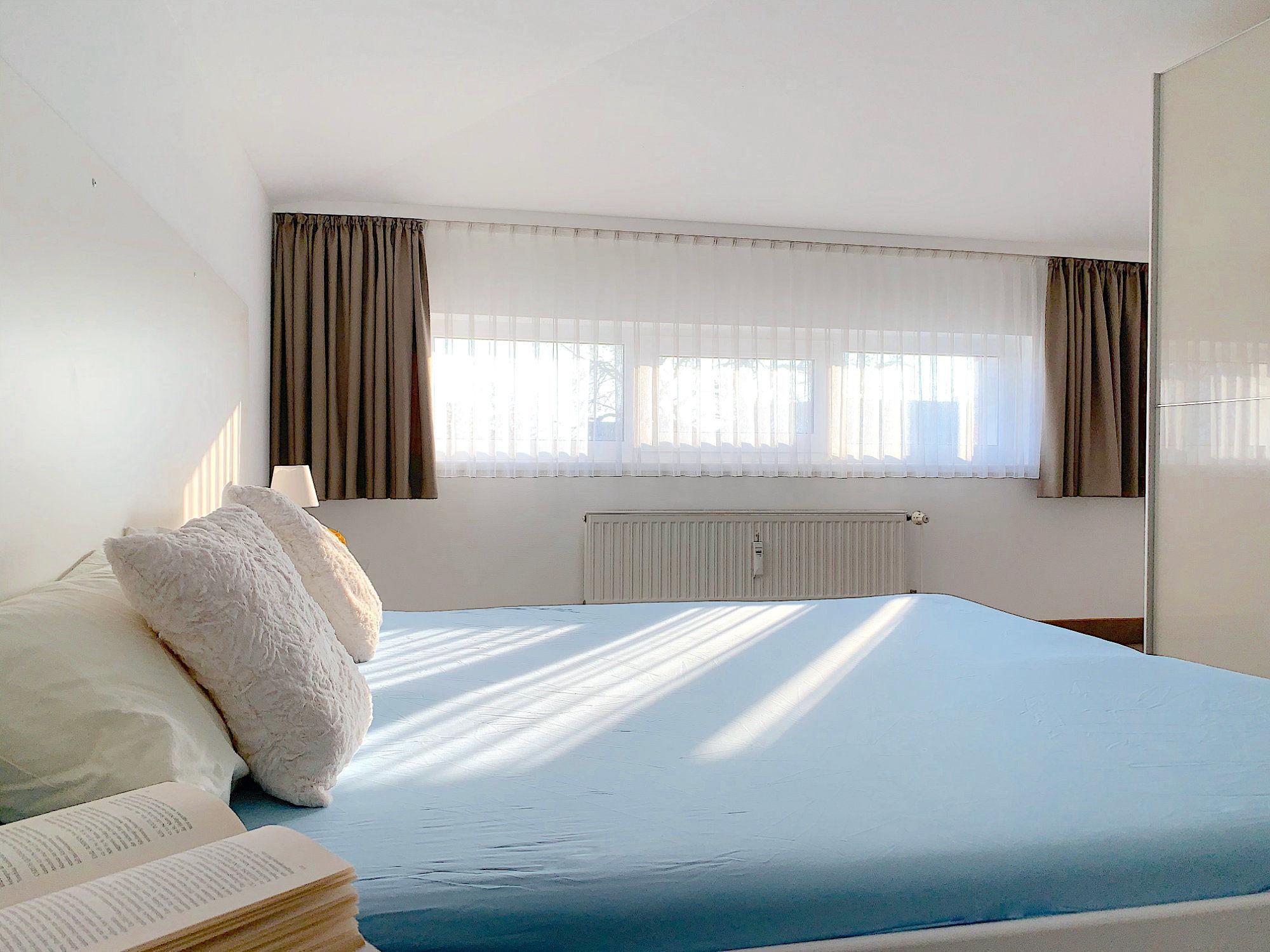 Schlafzimmer mit Doppelbett, rechts davon ein großer Kleiderschrank, im Hintergrund ein breites Fenster